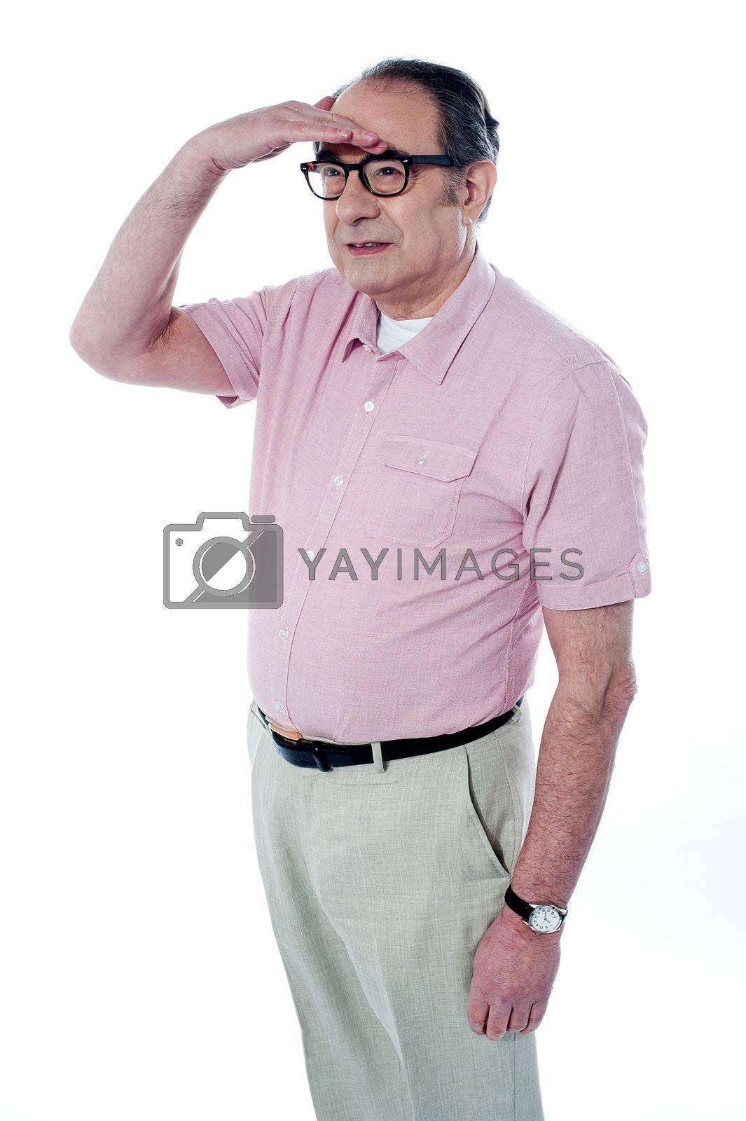 Old man looking far away by, studio shot