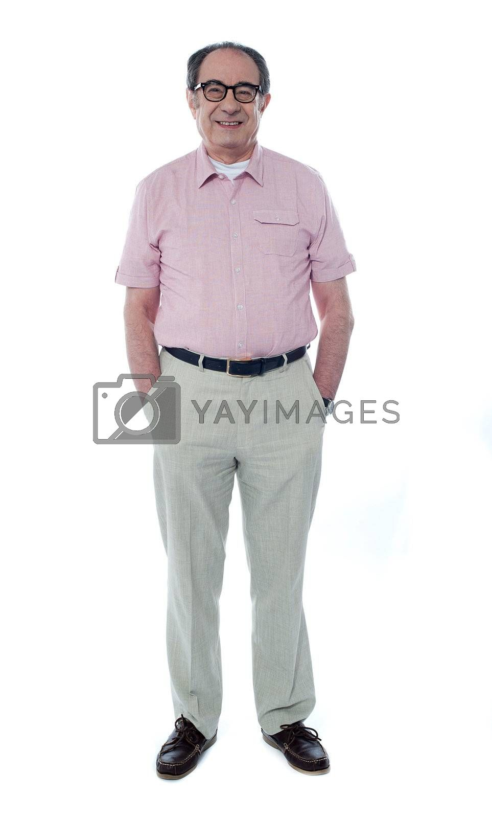 Smiling handsome senior member with hands in his pocket isolated on white