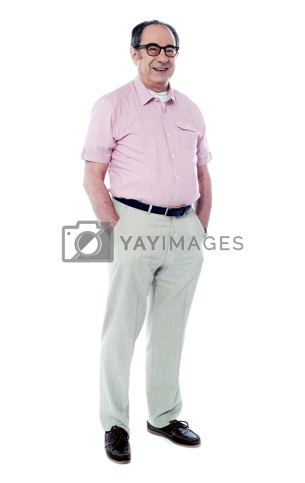 Joyful senior man posing casually with hands in pocket isolated on white