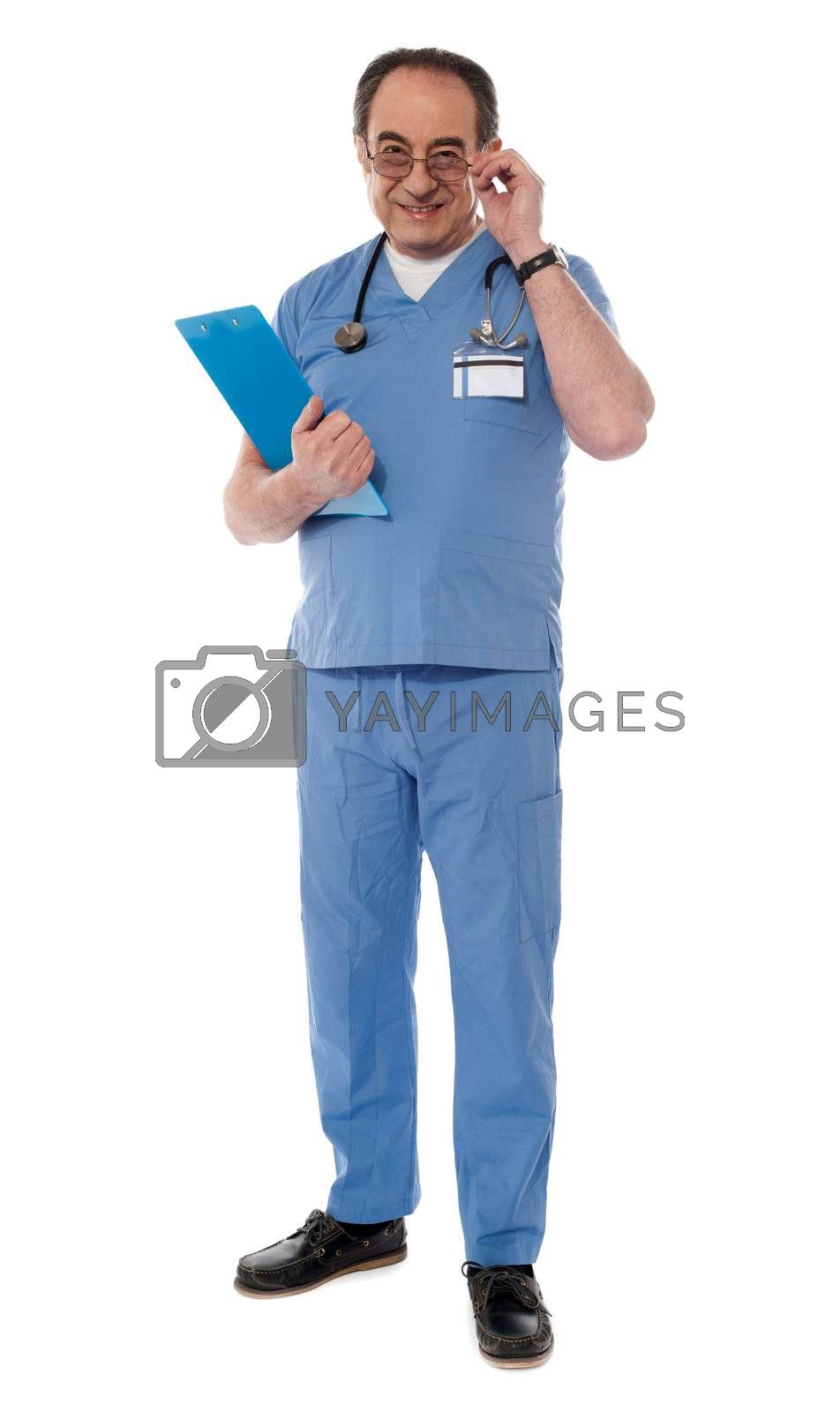 Medical professional looking at camera while holding his eyeglasses