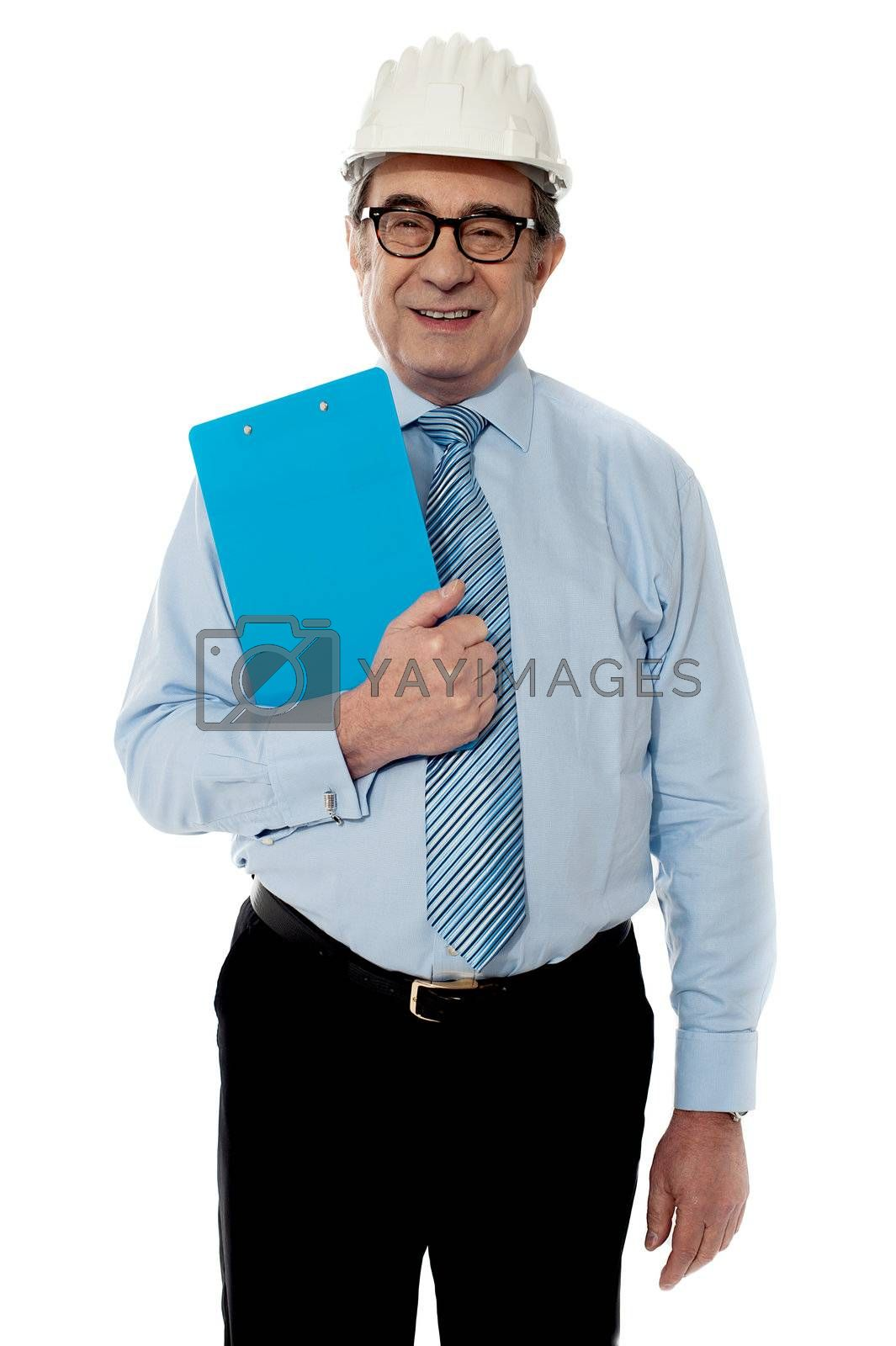 Smiling architect posing in front of camera wearing white hardhat with black trouser