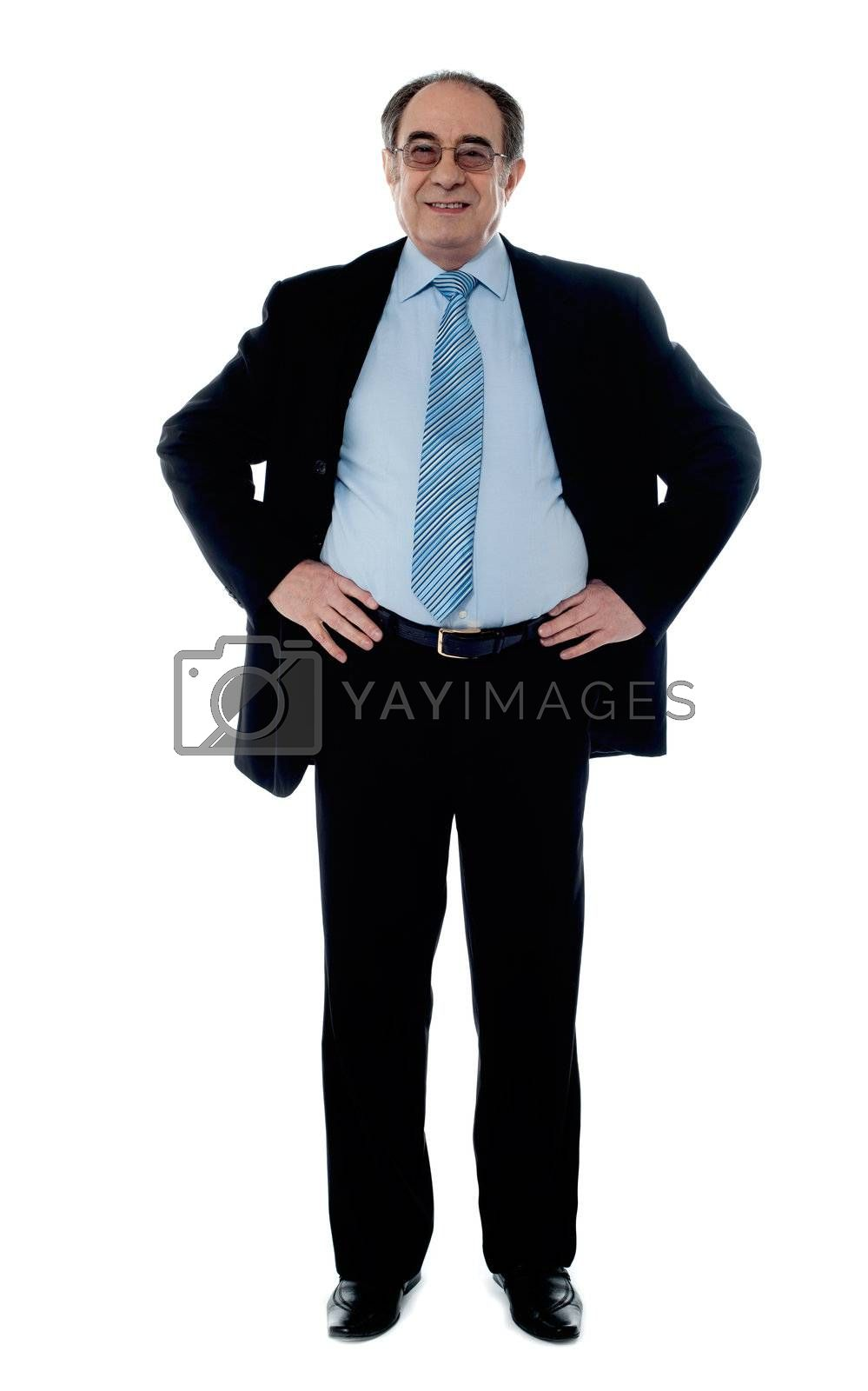 Senior manager poisng with hands on his waist, studio shot