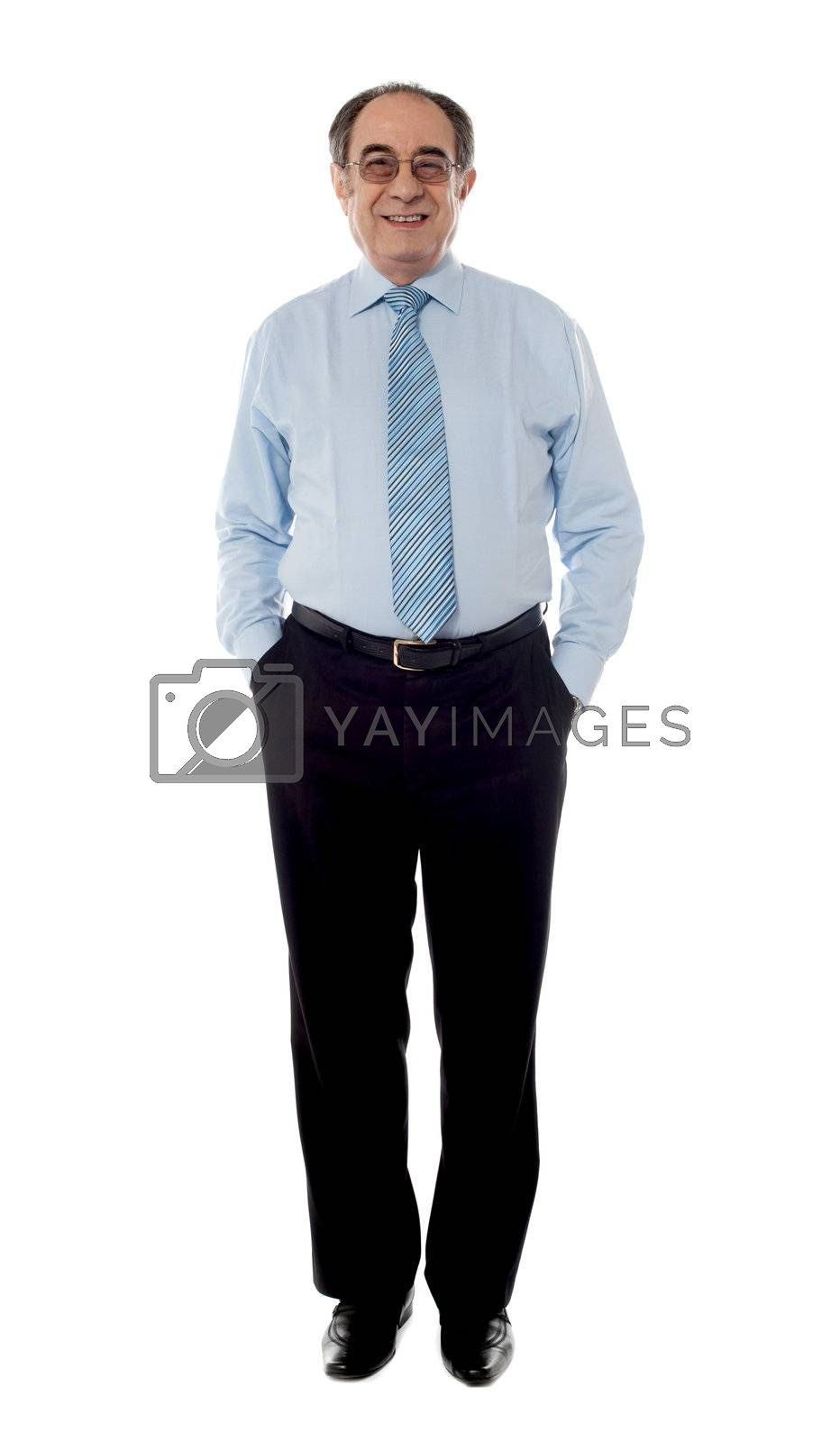 Matured businessman posing with arms in his pocket, looking at camera