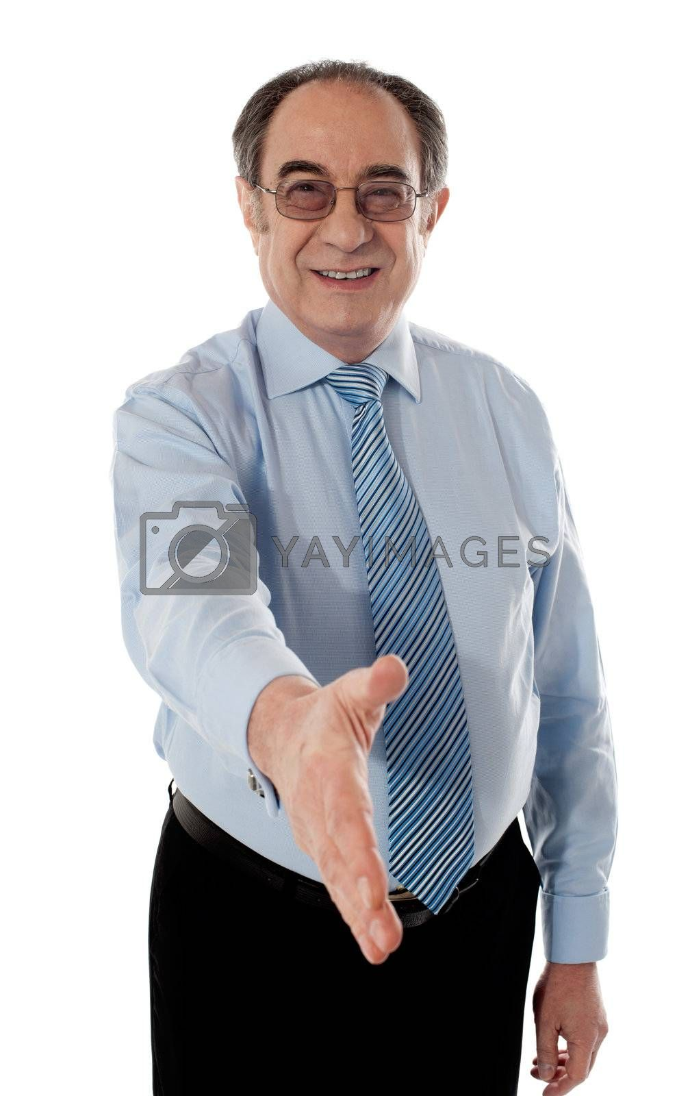 Businessman offering handshake to you, studio shot