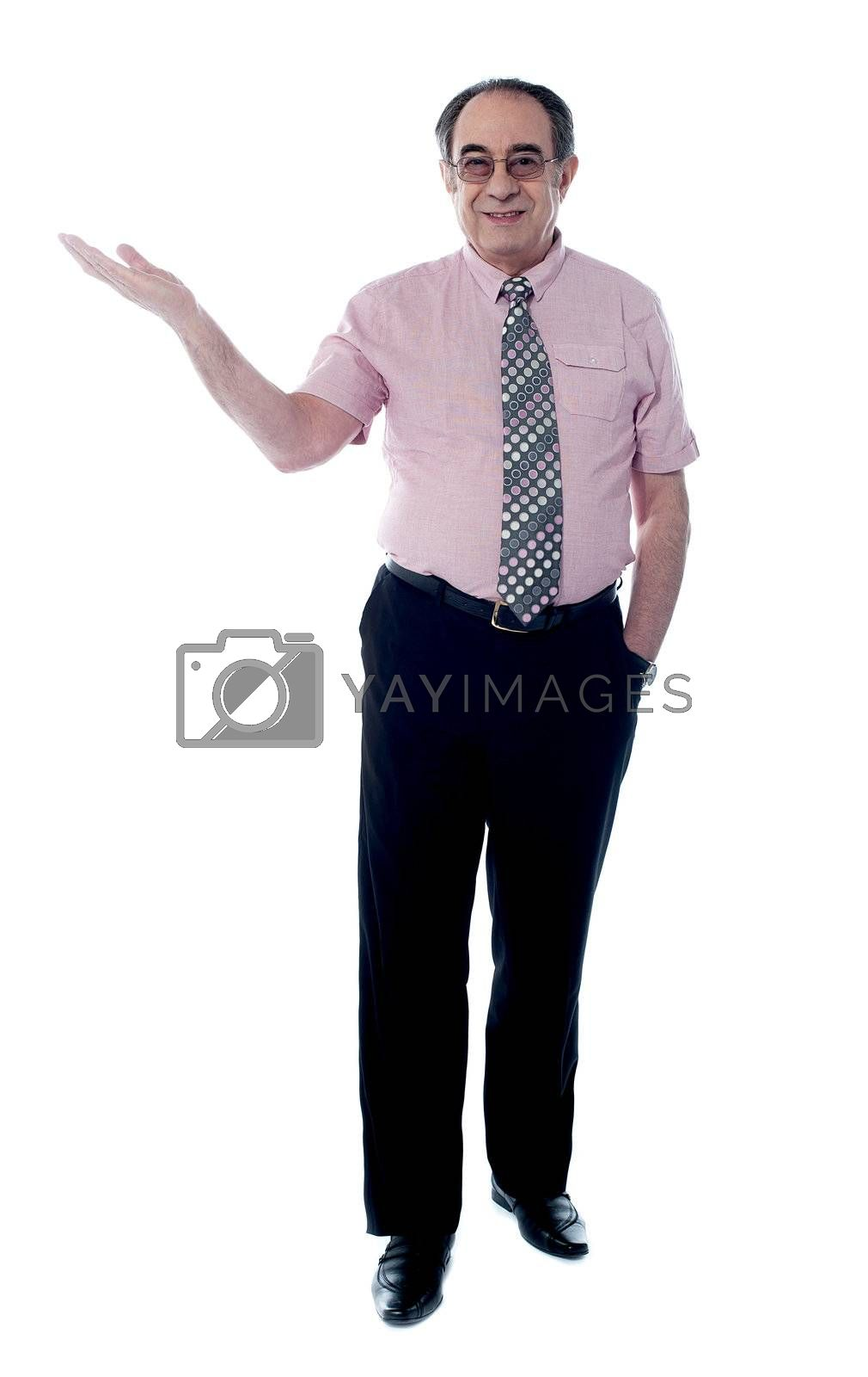 Senior boss posing with an open palm awith the other hand in pocket, stylish