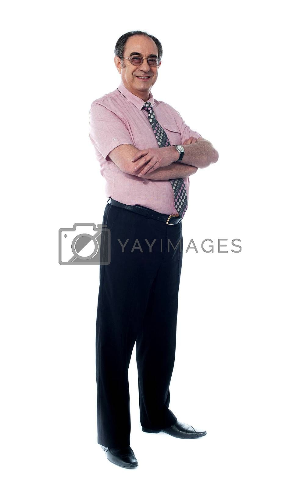 Senior business associate smiling as he poses with folded arms against white background