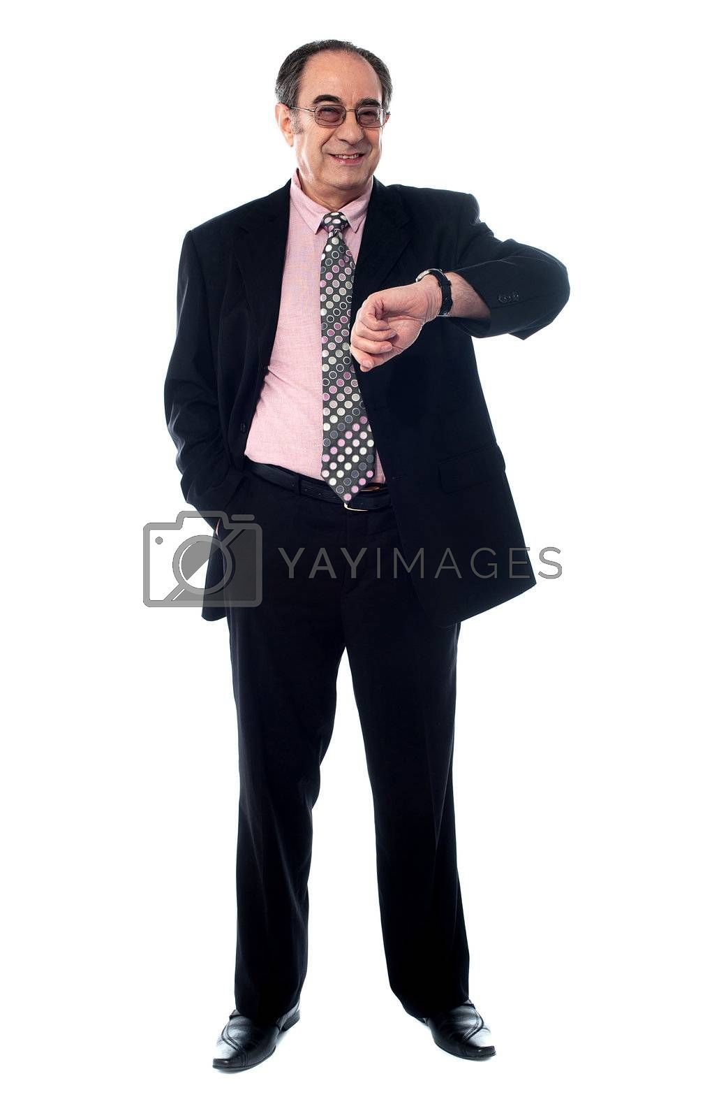 Senior businessperson smiling and taking a look at his watch