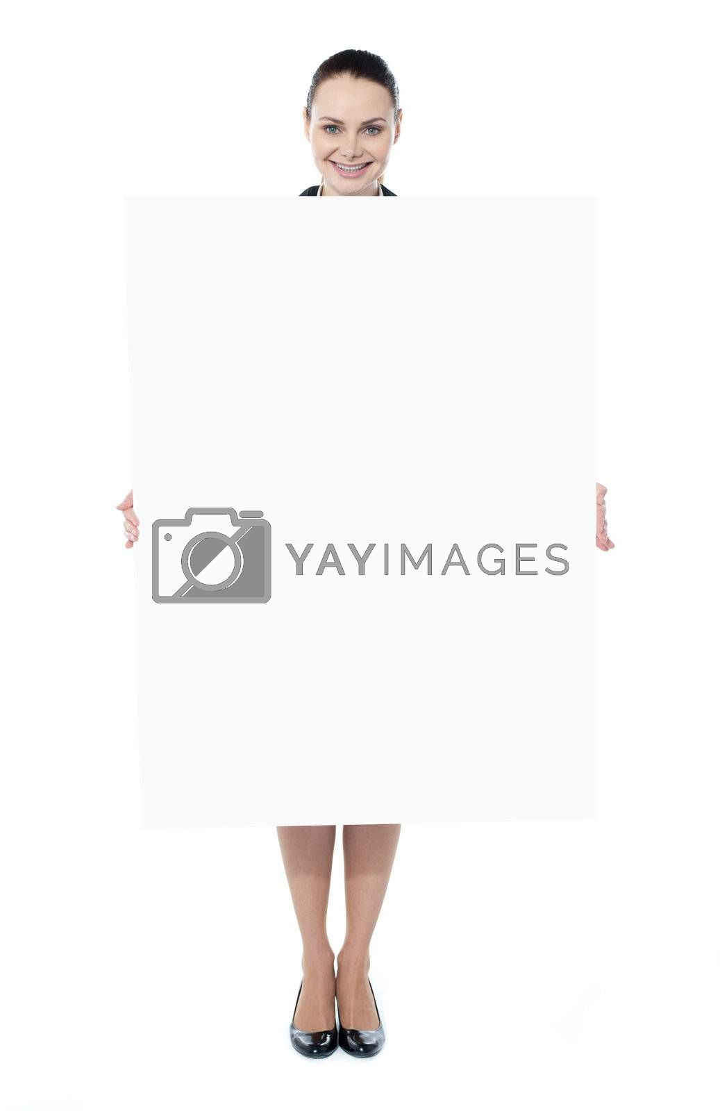 Portrait of a happy young woman holding blank billboard against white background
