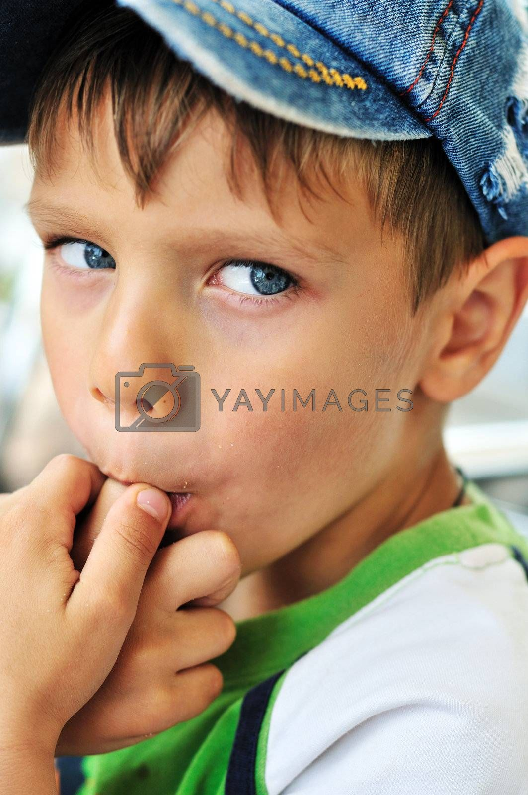 little boy licking his finger