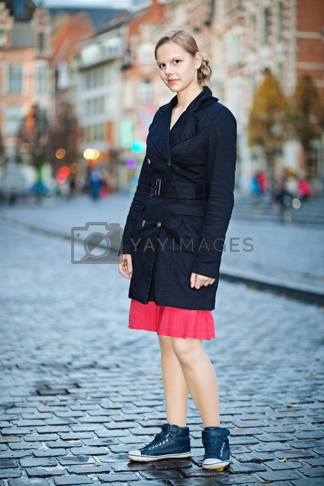 Pretty young woman standing on an old city square in twilight