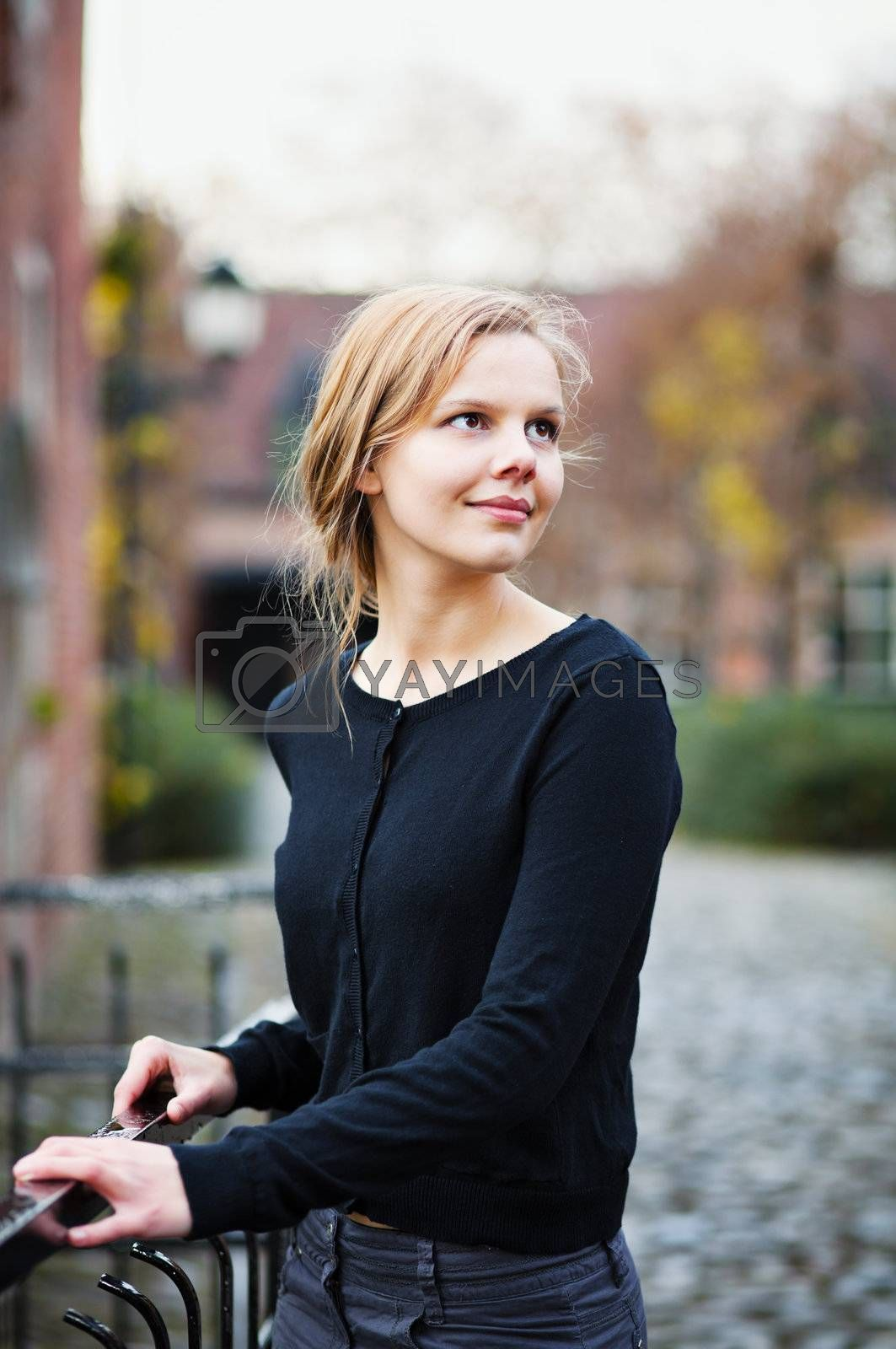 Portrait of a pretty young blond woman standing on a bridge in and turning back