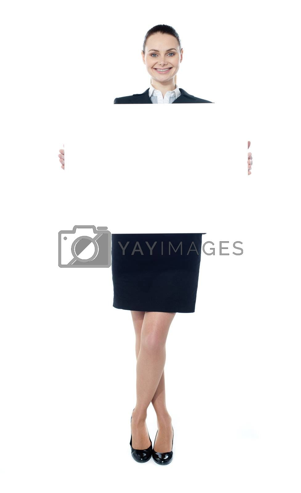 Portrait of a happy young woman holding a blank billboard over white background