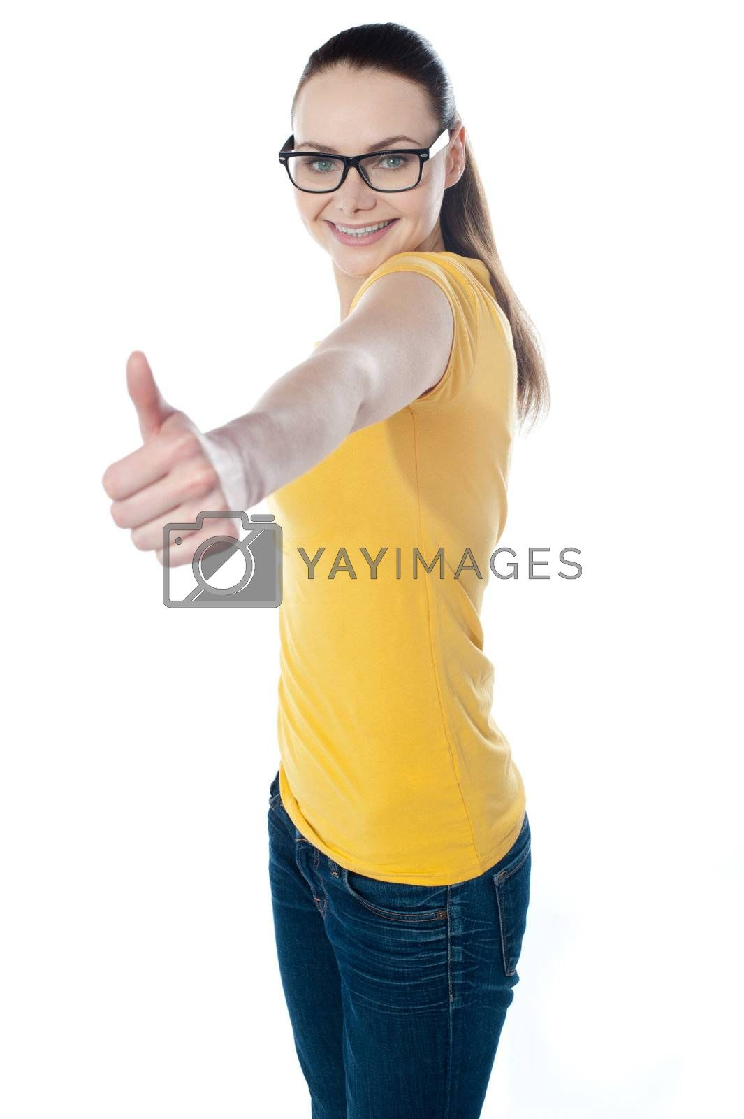 Glamourous teenager gesturing thumbs-up isolated on white