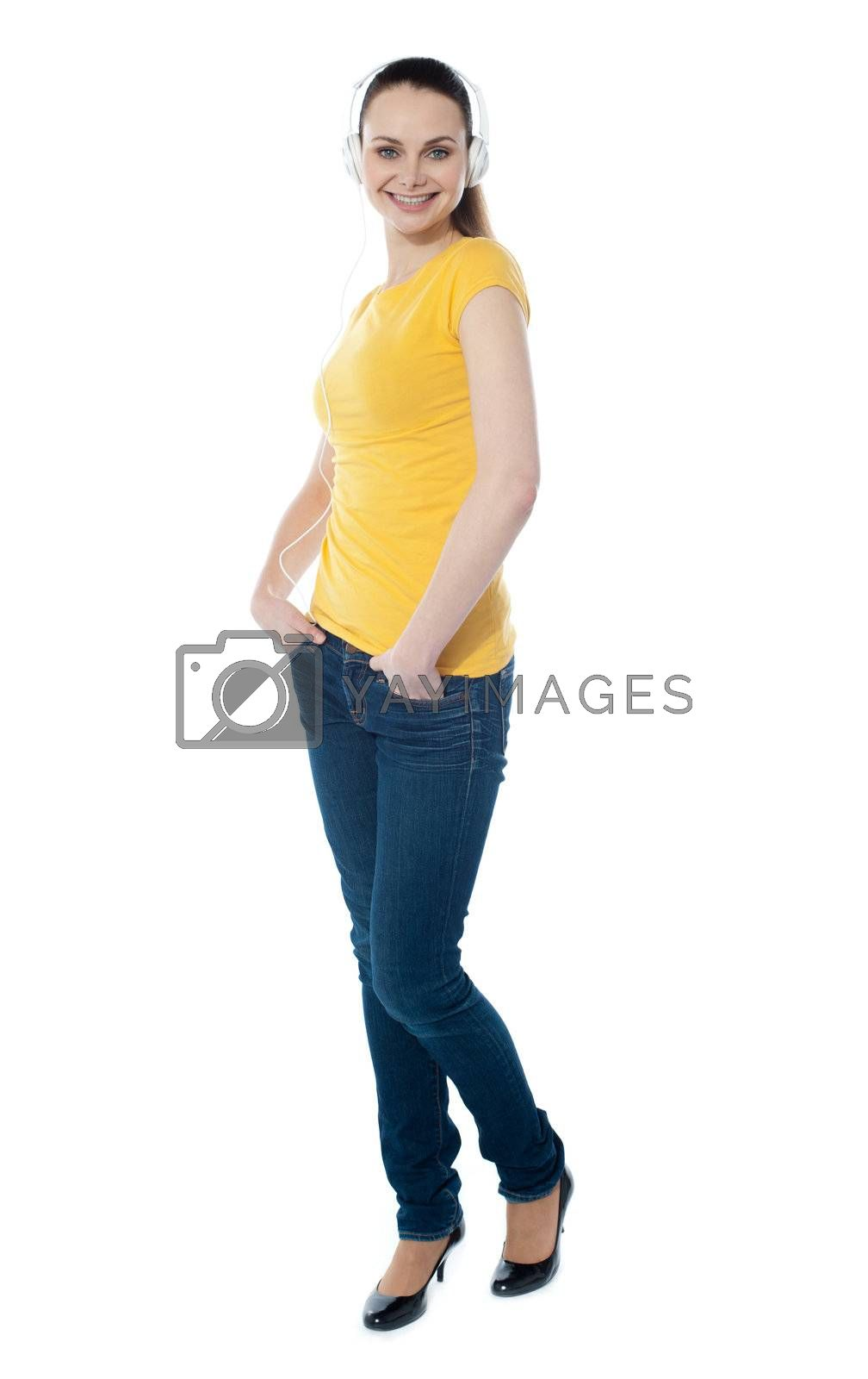 Stylish teenager enjoying music and posing with hands in pocket