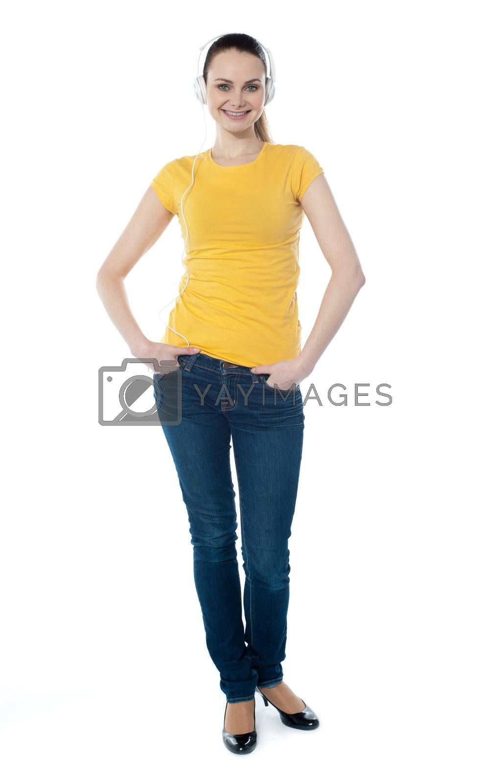 Portrait of a cute young girl standing with hands in pocket over white background