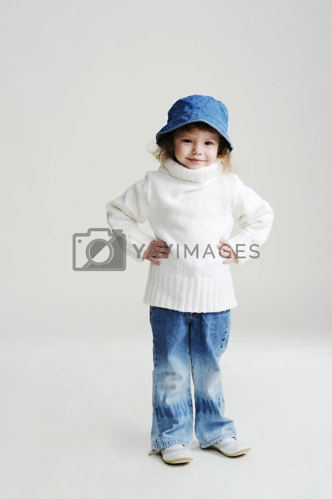 An image of a little girl in a blue hat and white jumper