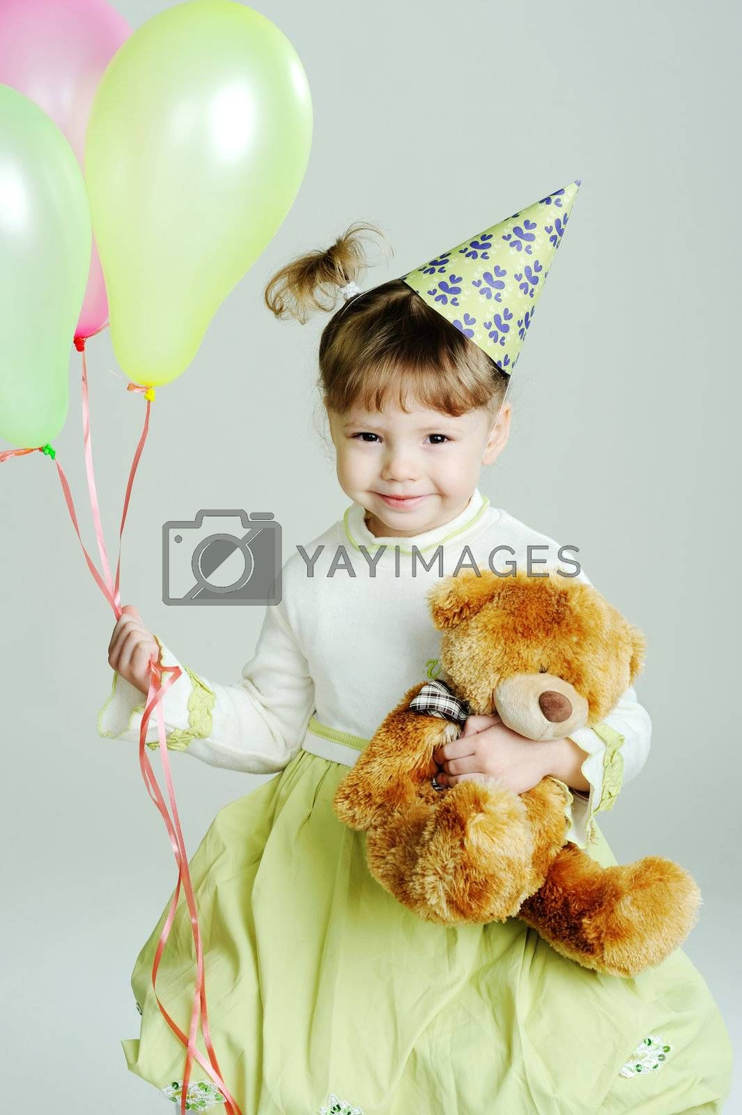 A portrait of a little girl with a teddy-bear and balloons