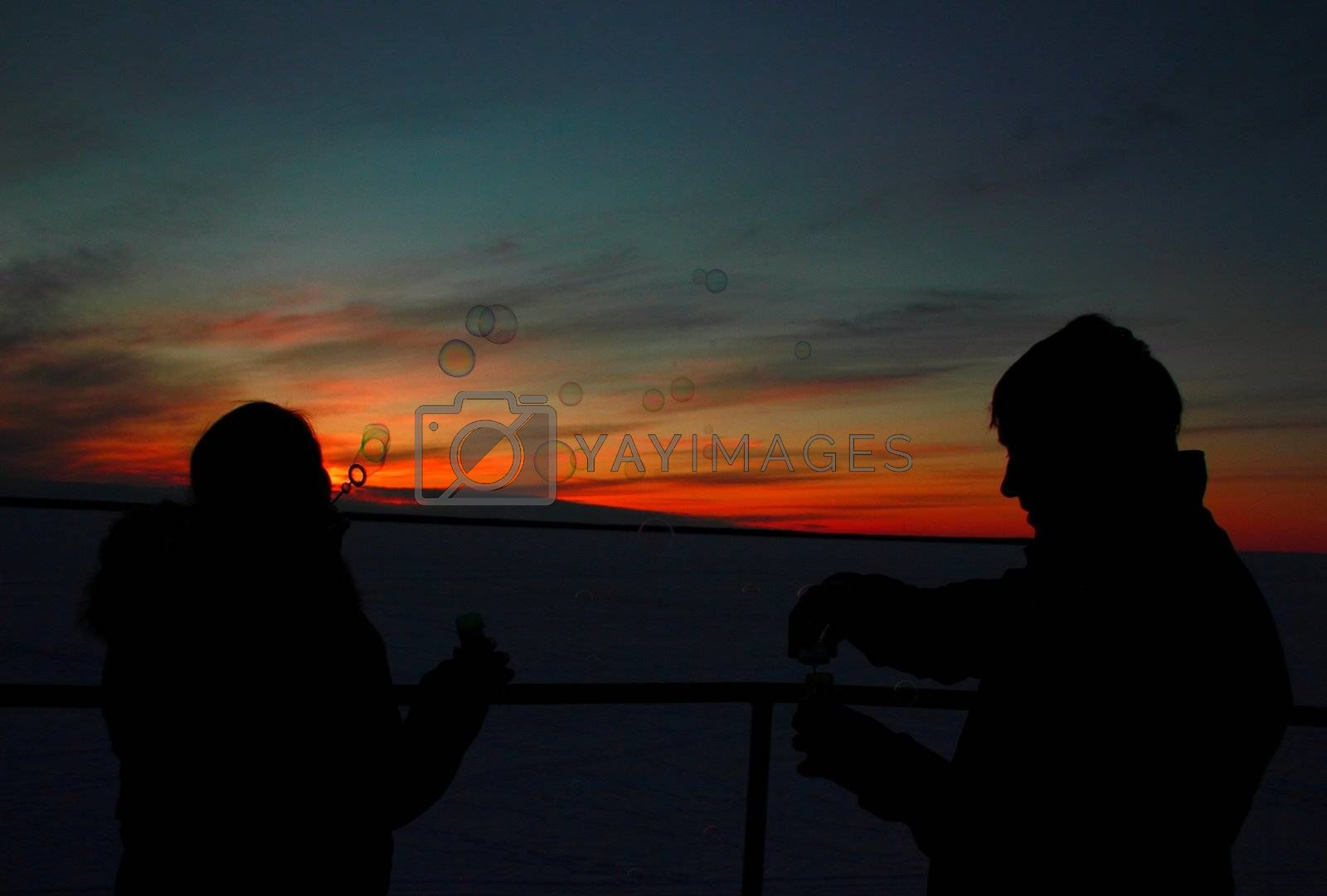Silhouettes of the loving couple at sunset, blow bubbles