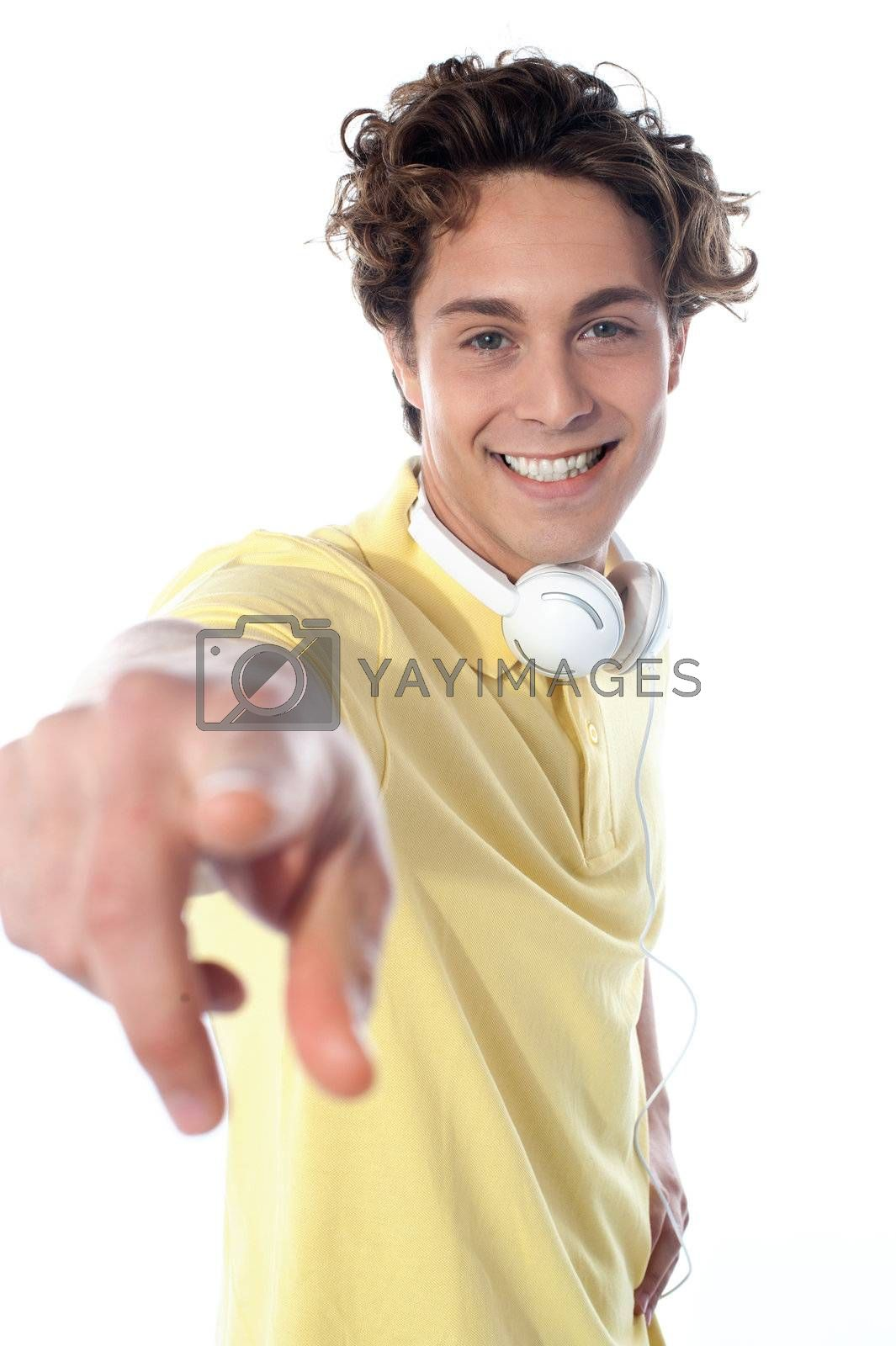 Guy with headphones enjoying music, pointing at you