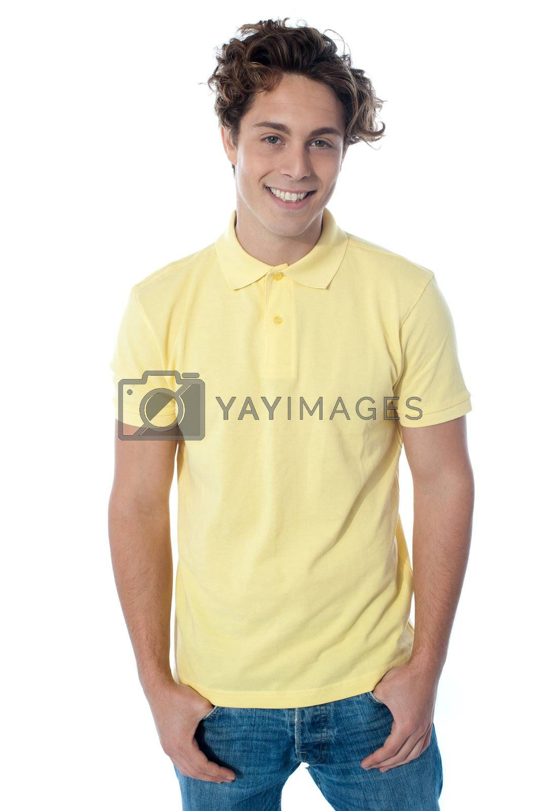 Portrait of a stylish young man standing with hands in pockets over white background