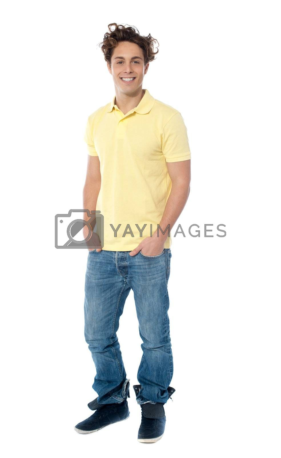 Casual young man standing with hands in pocket against white background