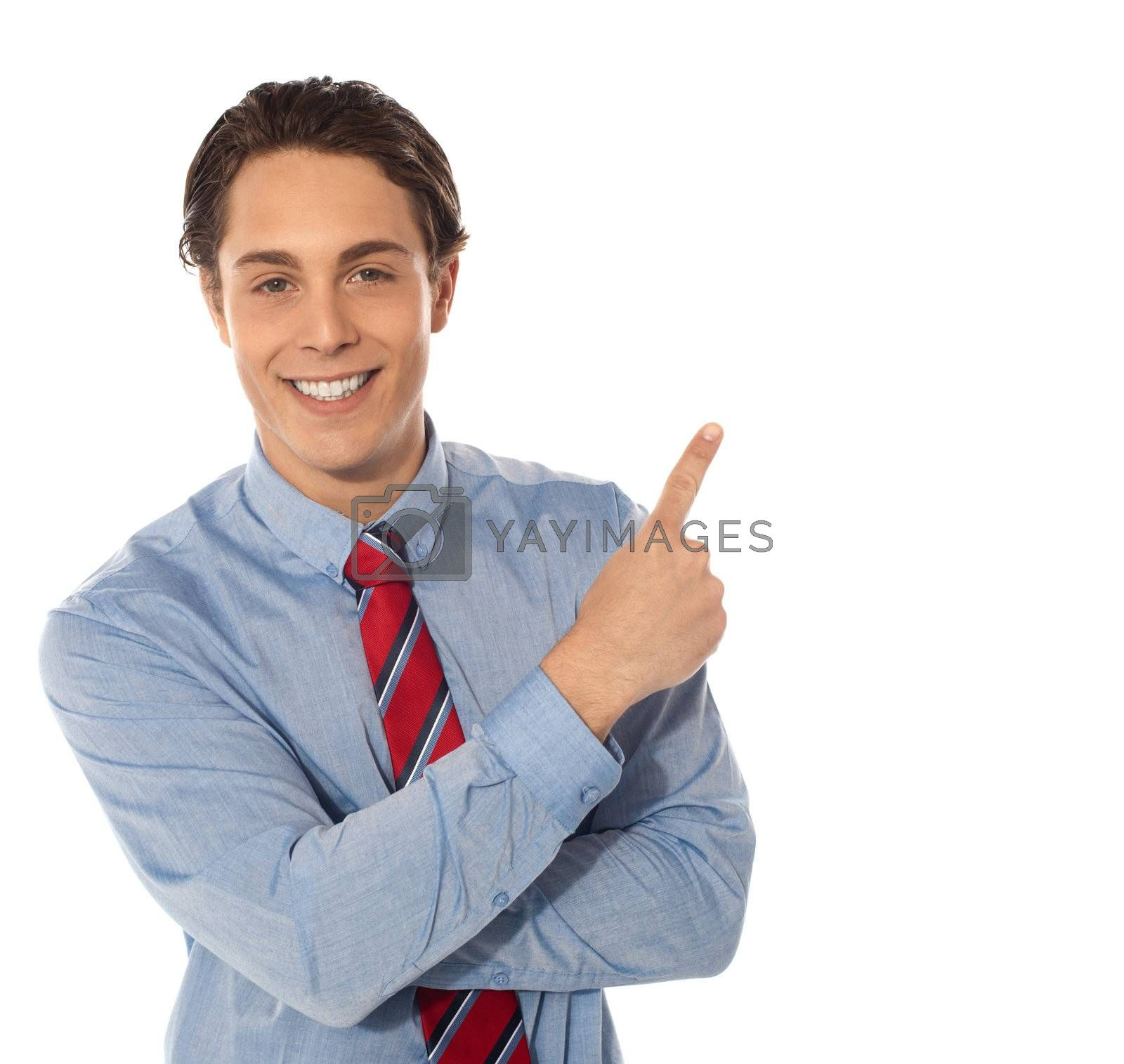 Business male pointing upwards and smiling at camera