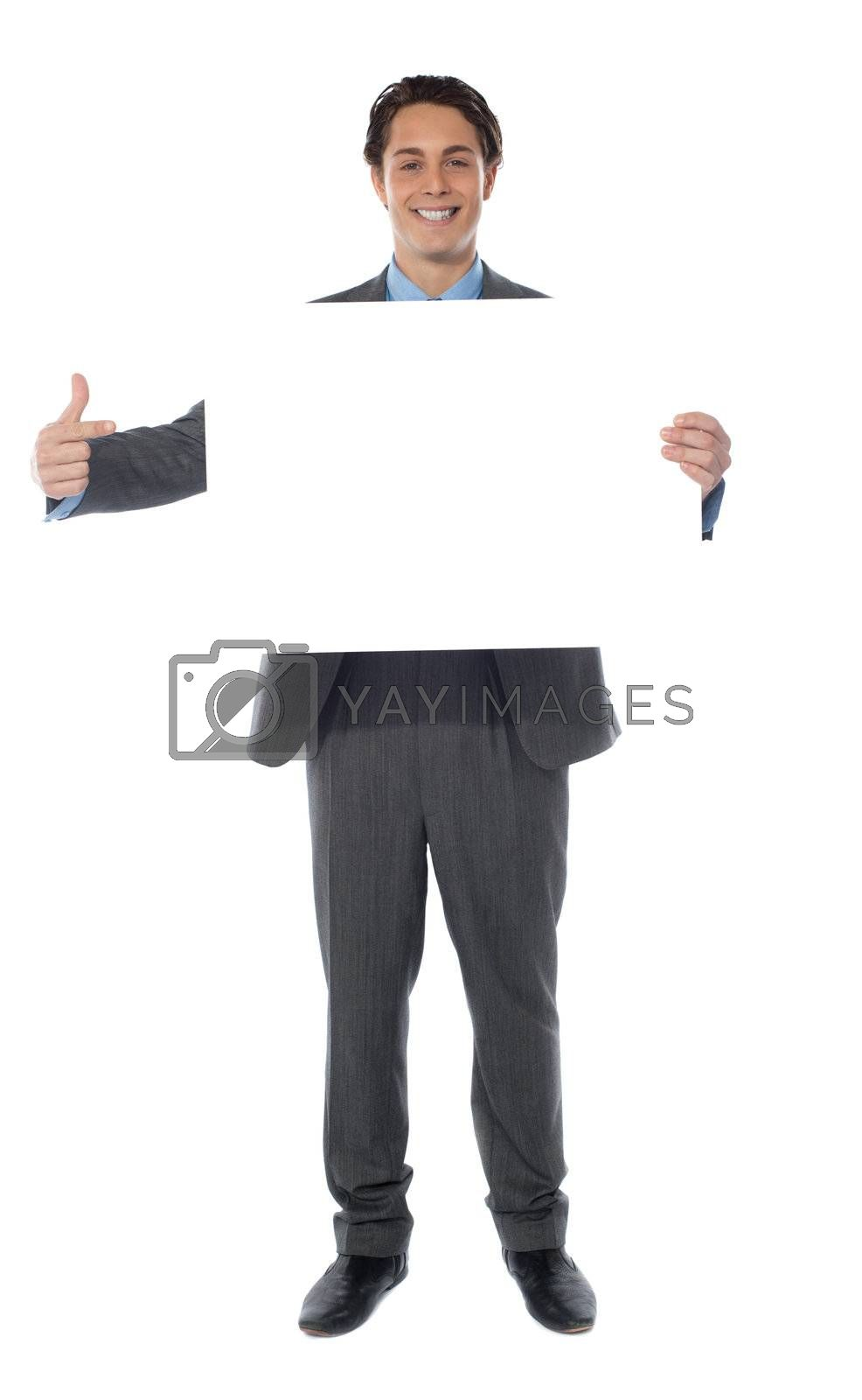 Business professional pointing towards an empty billboard, smiling at camera