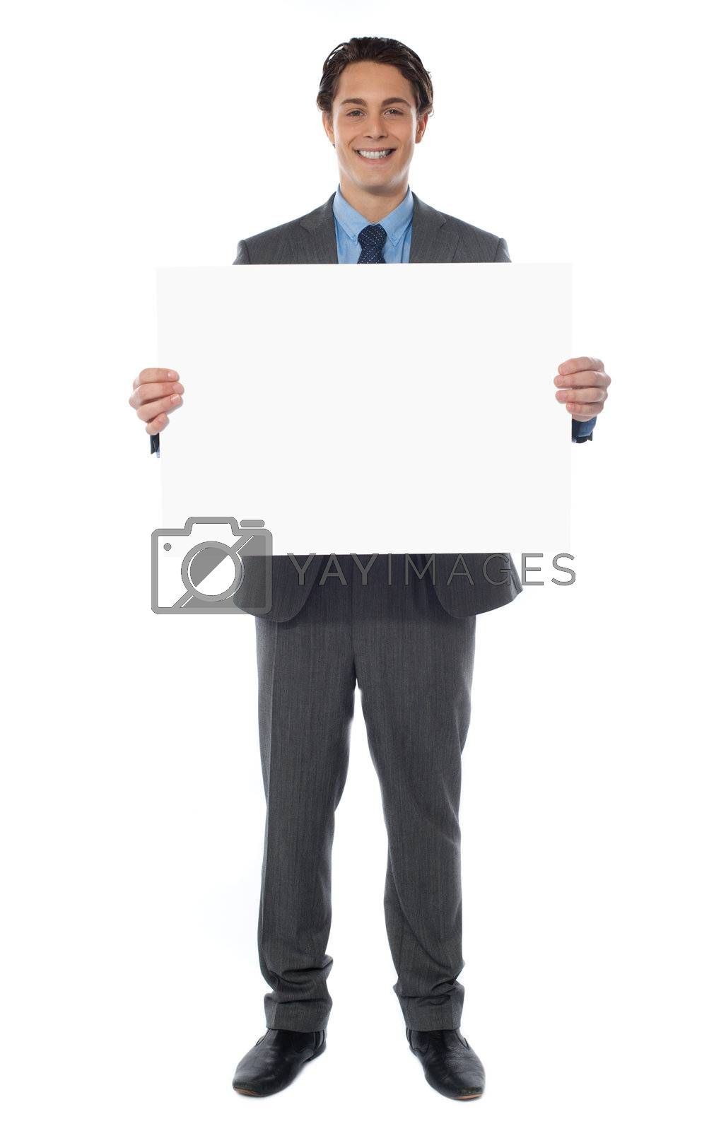 Young businessman holds the blank billboard, full-length view