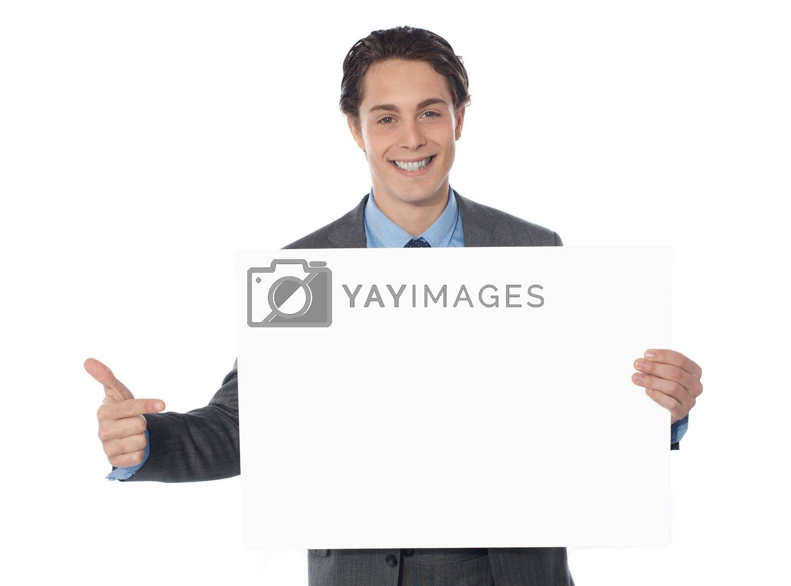 Male executive pointing towards blank billboard isolated on white