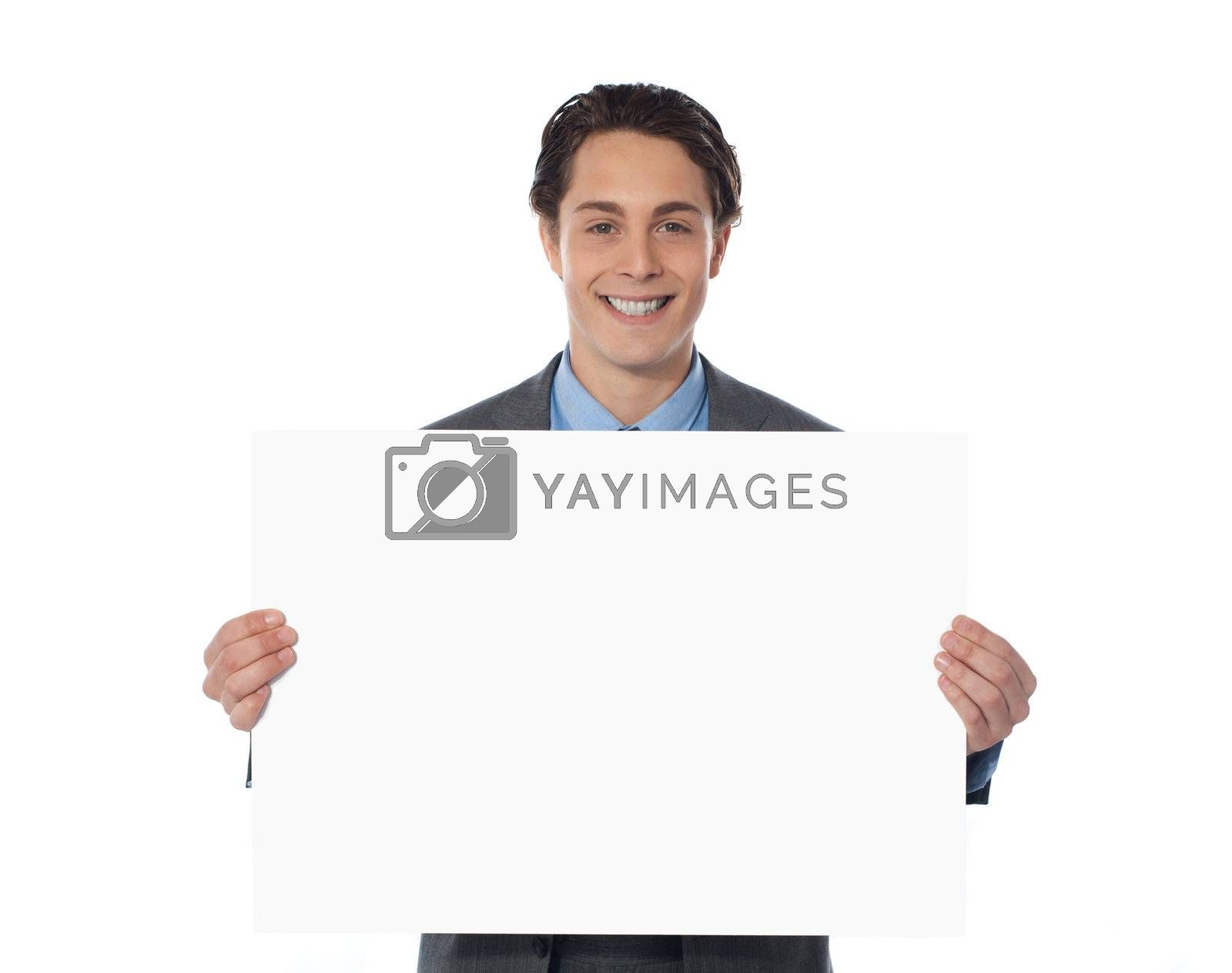 Portrait of a happy businessman showing an emty billboard against white background