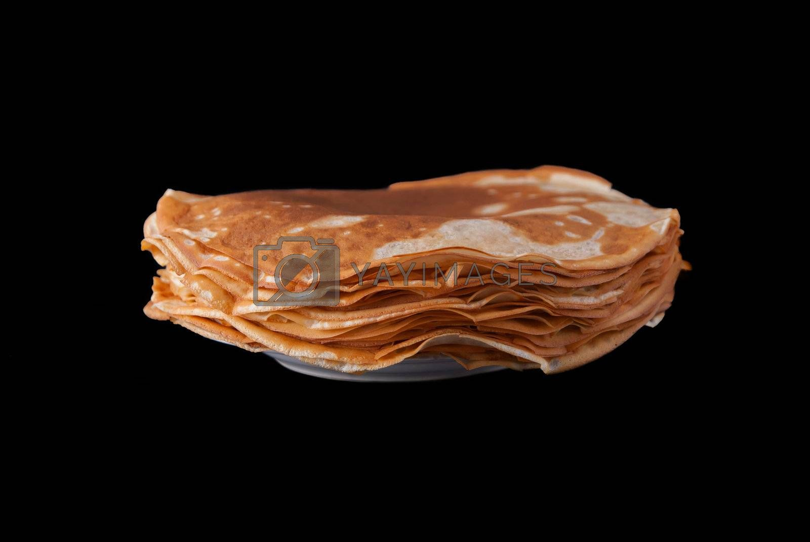 Russian pancakes pile on plate, isolated on black background