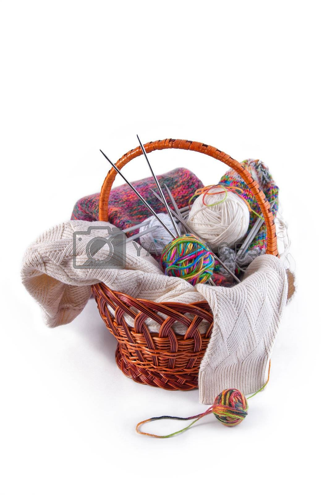 Balls of wool and knitting needles in basket isolated on a white background