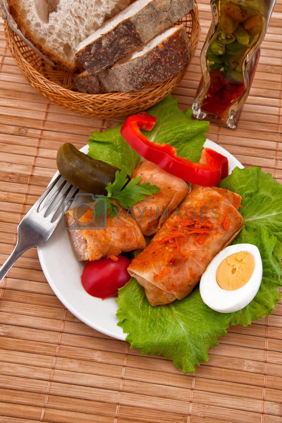 Stuffed cabbage on plate, fork and bread