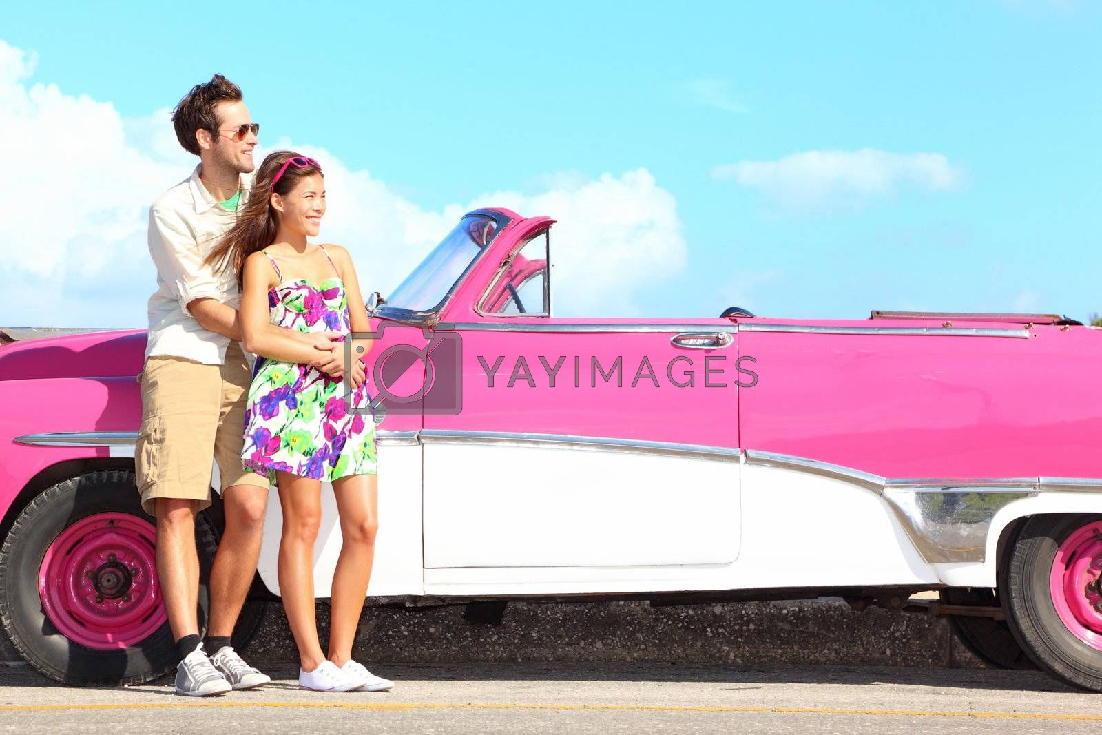 Couple and vintage retro car. Happy smiling young couple standing by pink old vintage car during summer road trip travel in Havana, Cuba. Interracial couple, Asian woman, Caucasian man.
