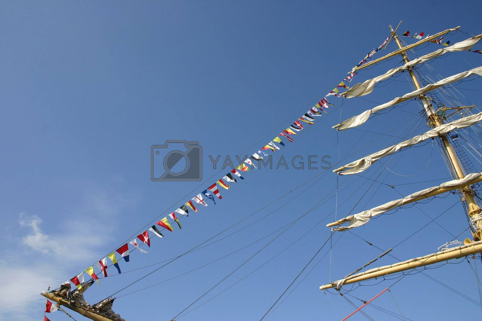 Sailing vessel with white sails on a mast and alarm flags