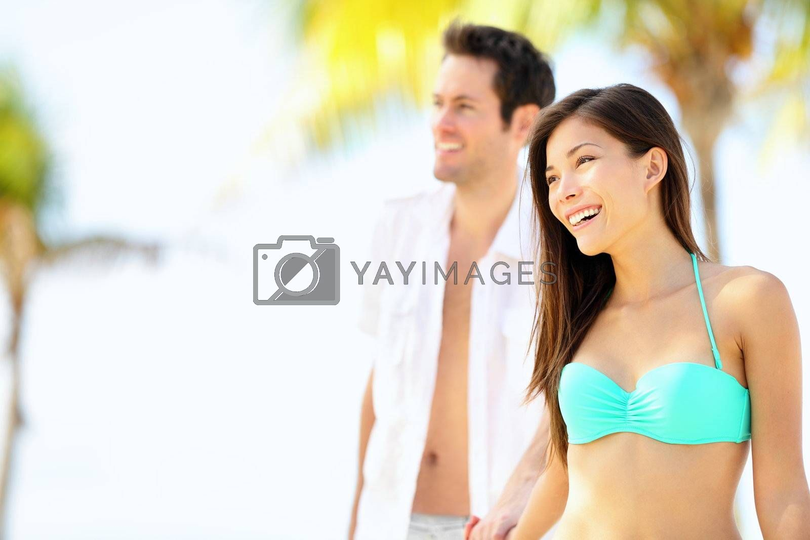 Happy couple on beach vacation travel walking under the sun on sunny summer day. Young beautiful interracial couple, Asian woman, Caucasian man.