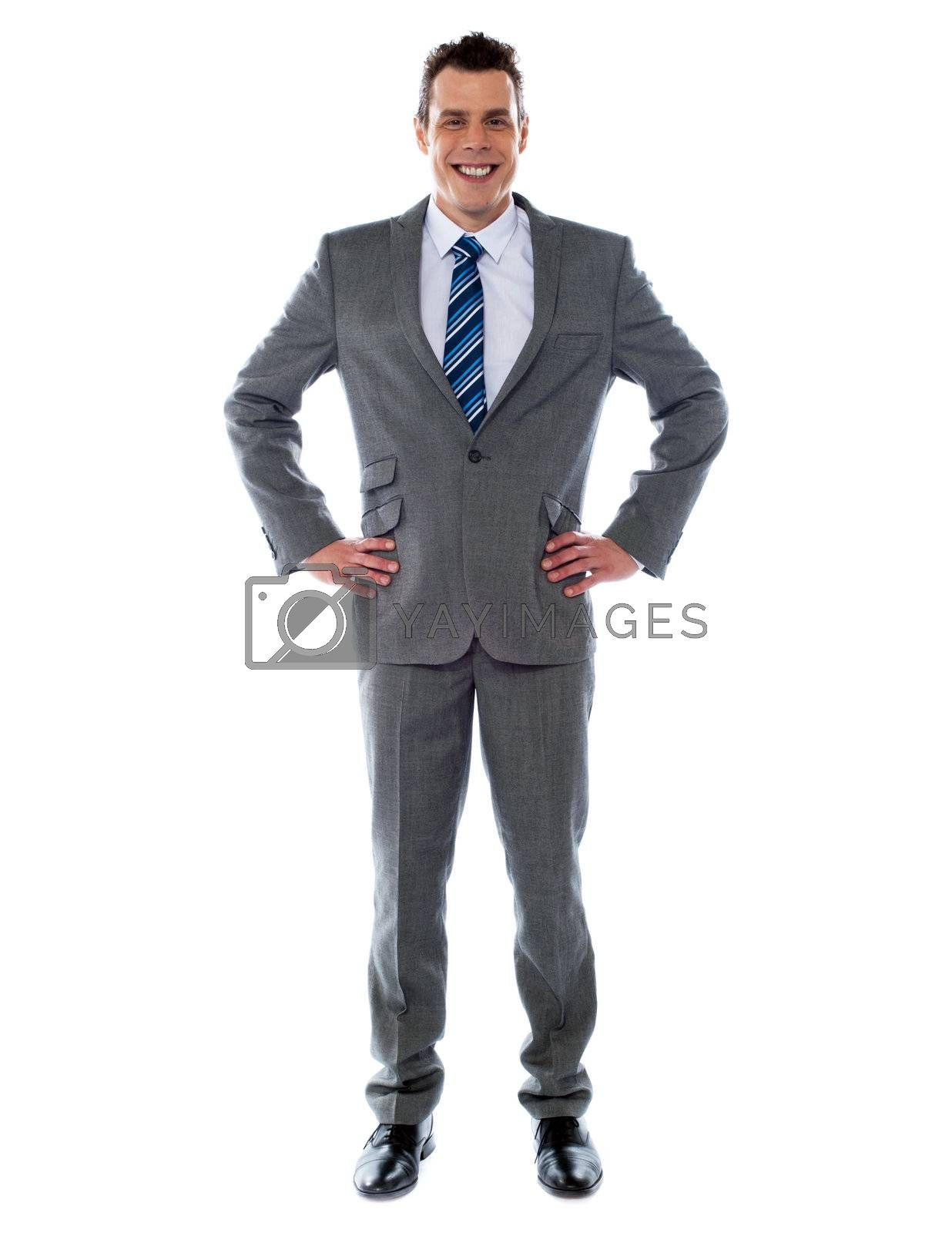 Confident young business executive poisng with hands on his waist, studio shot