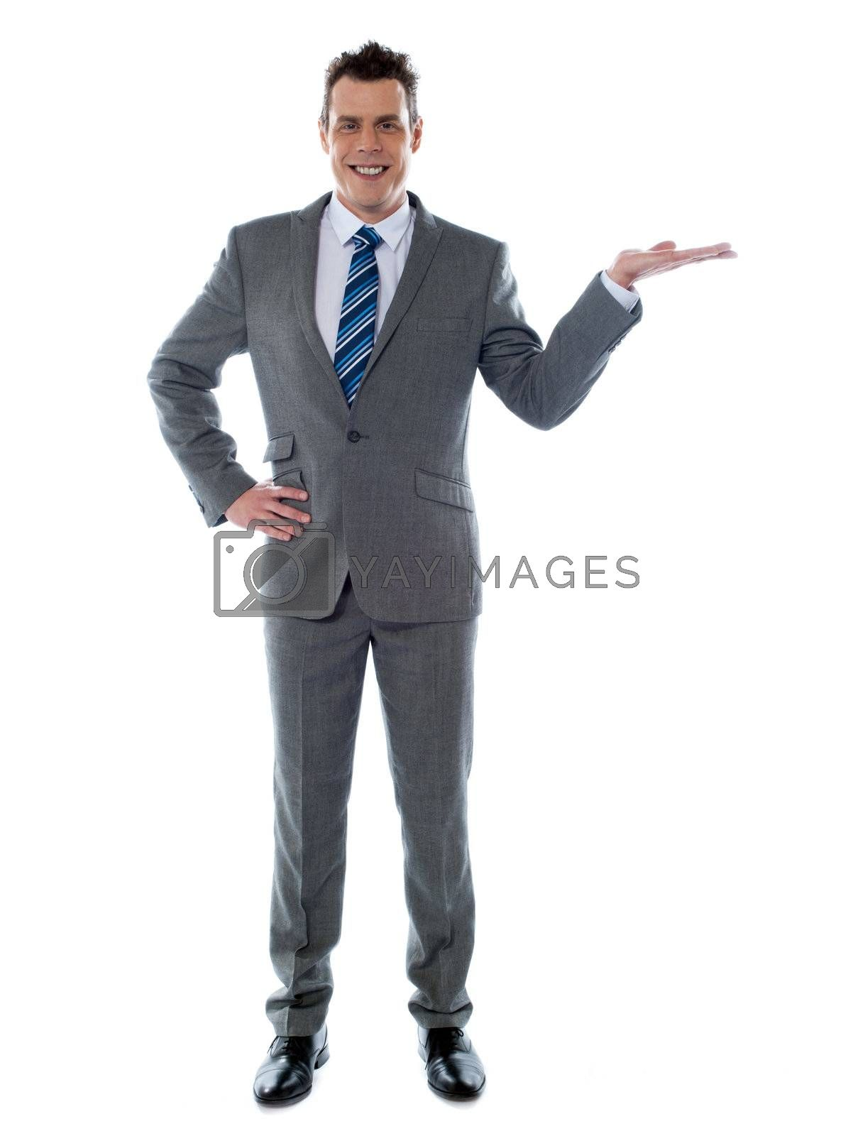 Portrait of a happy young businessman presenting a product against white background - copyspace