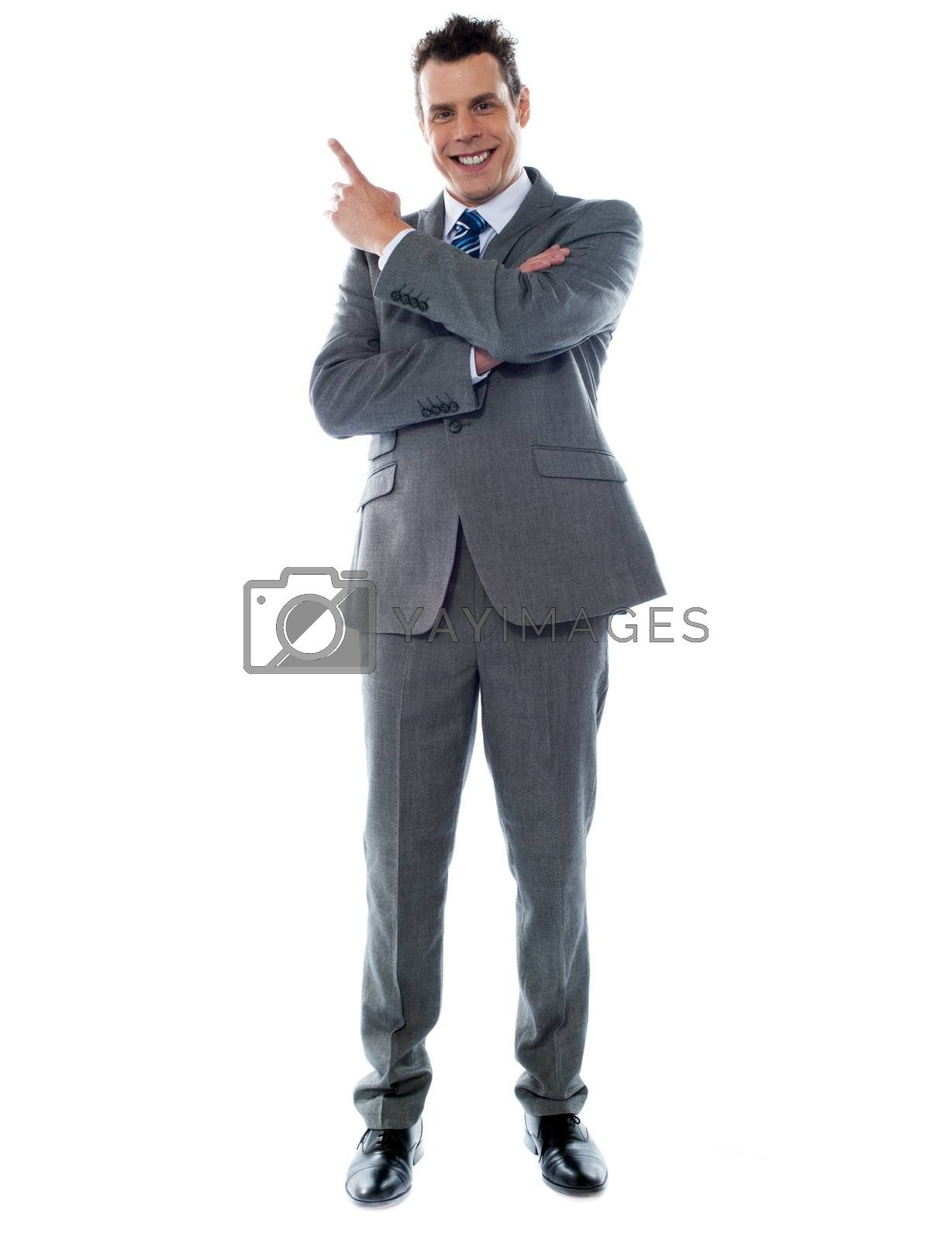 Full length of young businessman in suit pointing at copyspace over white background