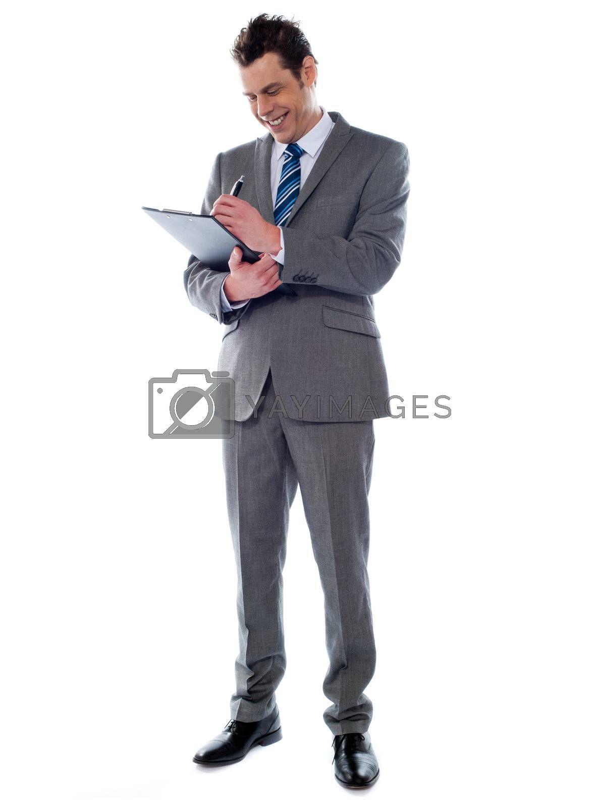 Portrait of a successful businessman writing notes on clipboard isolated on white background