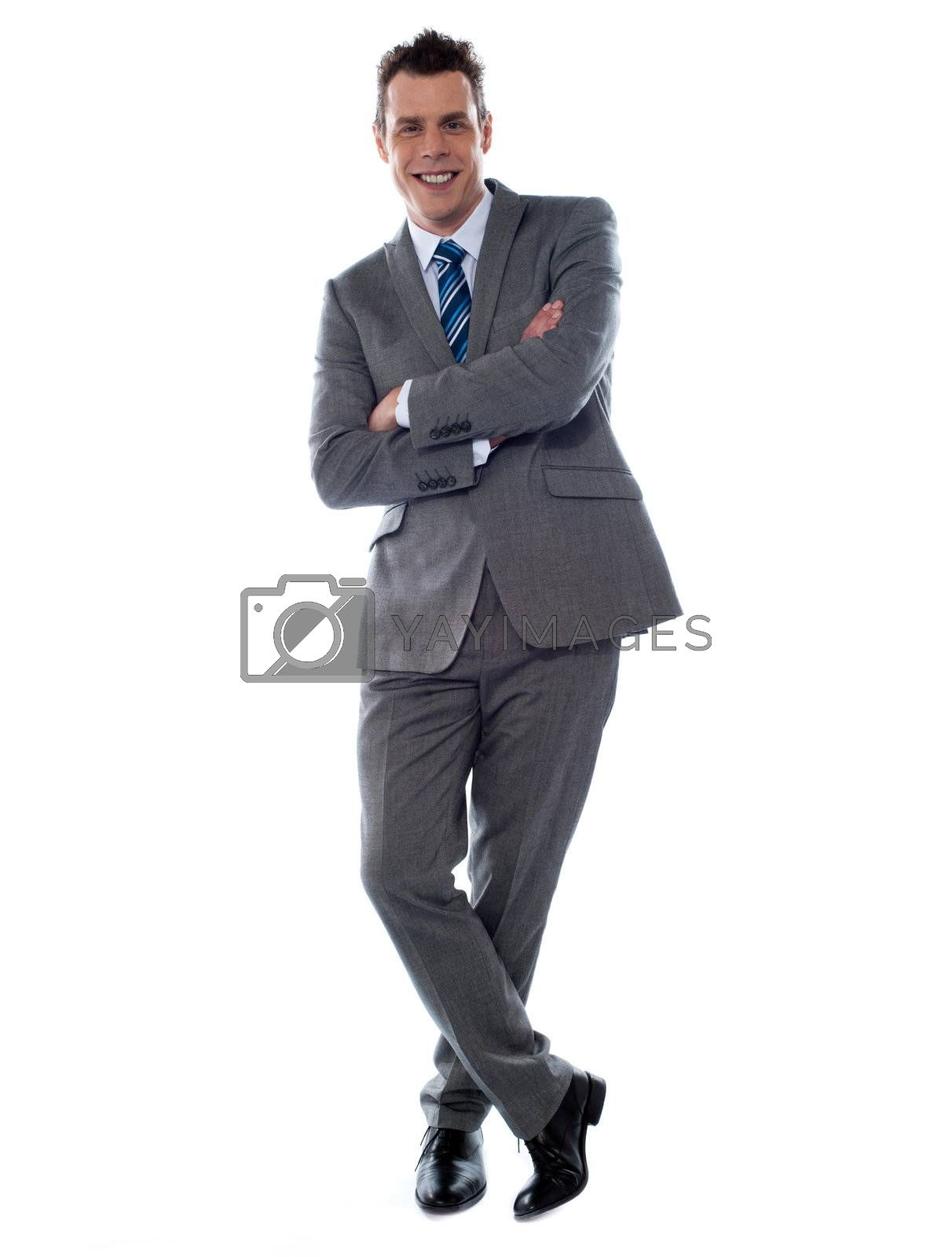 Cheerful young businessman leans against wall. Isolated on white background