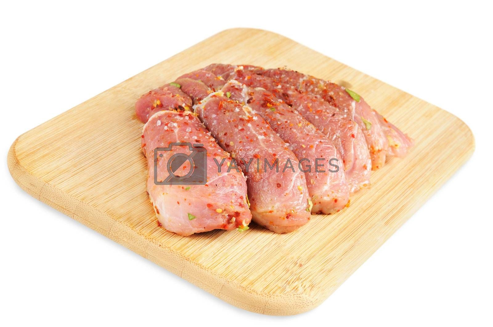 Raw meat, with spices on wooden board. Isolated on white.