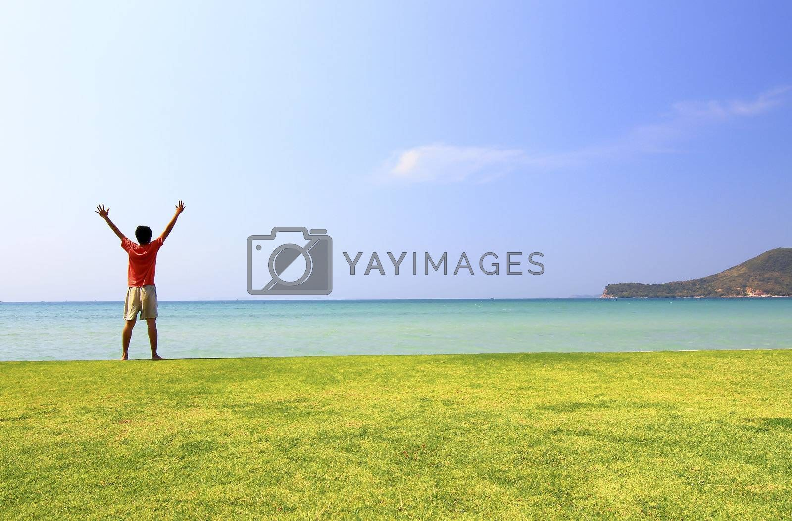 happy man on the meadow against the sea landscape
