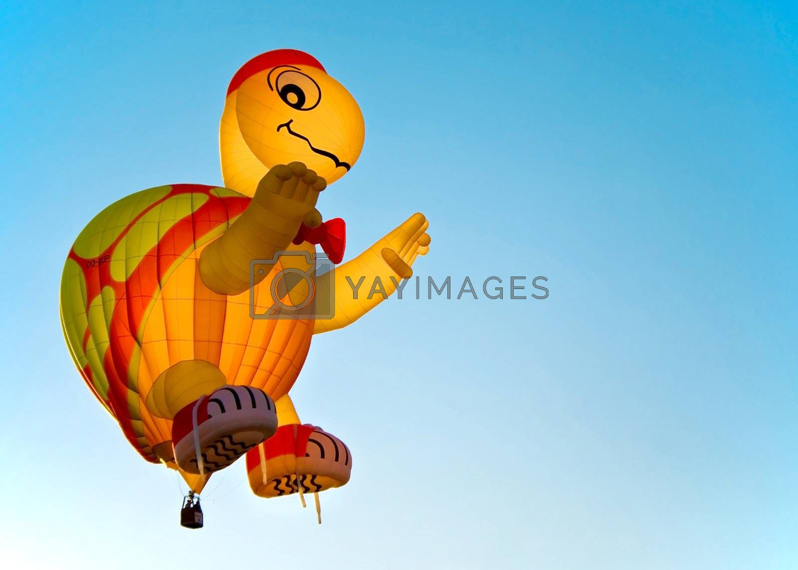 A turtle air balloon against a clear blue sky at the festival.