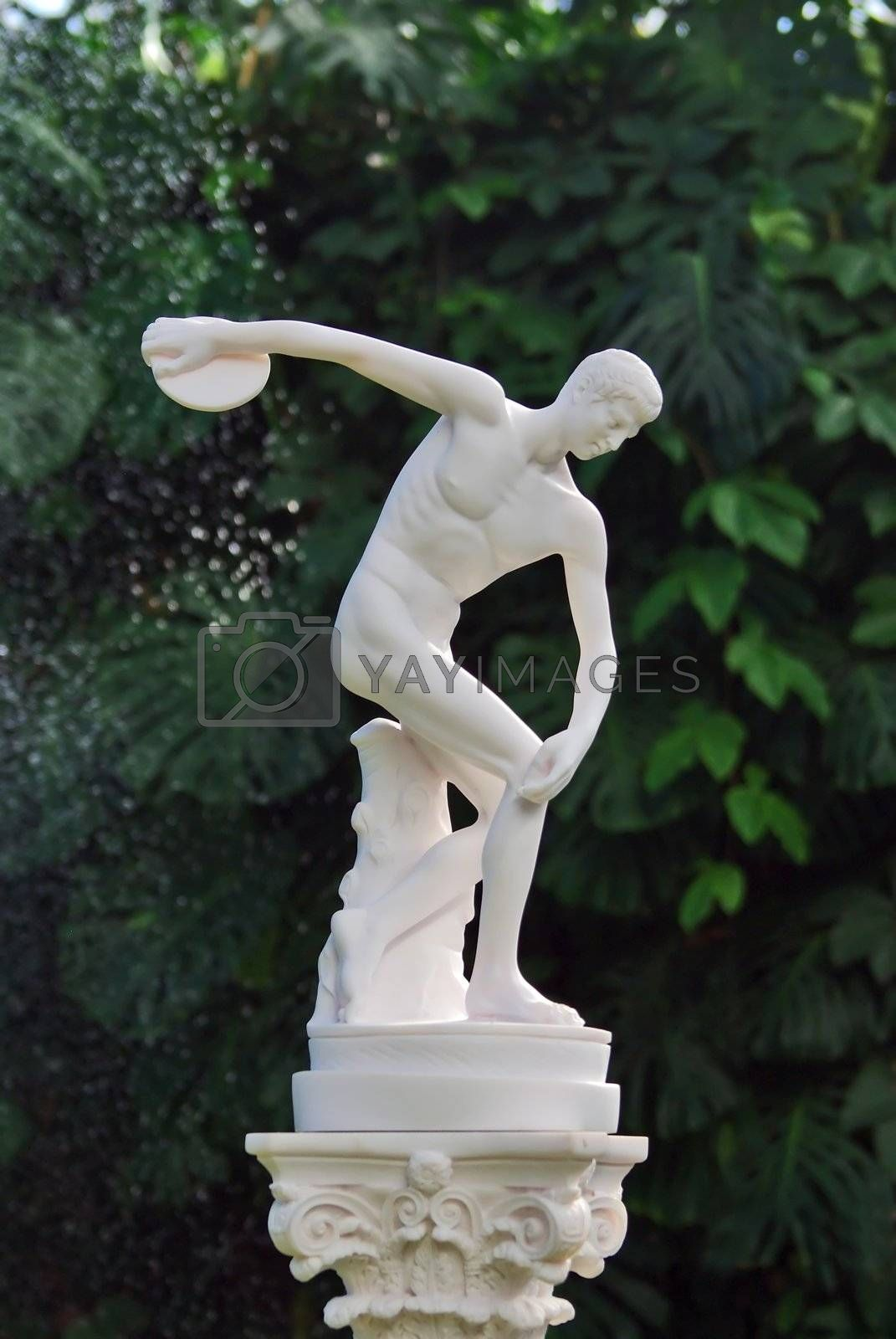 The sculpture of discobolus in park over green leaves