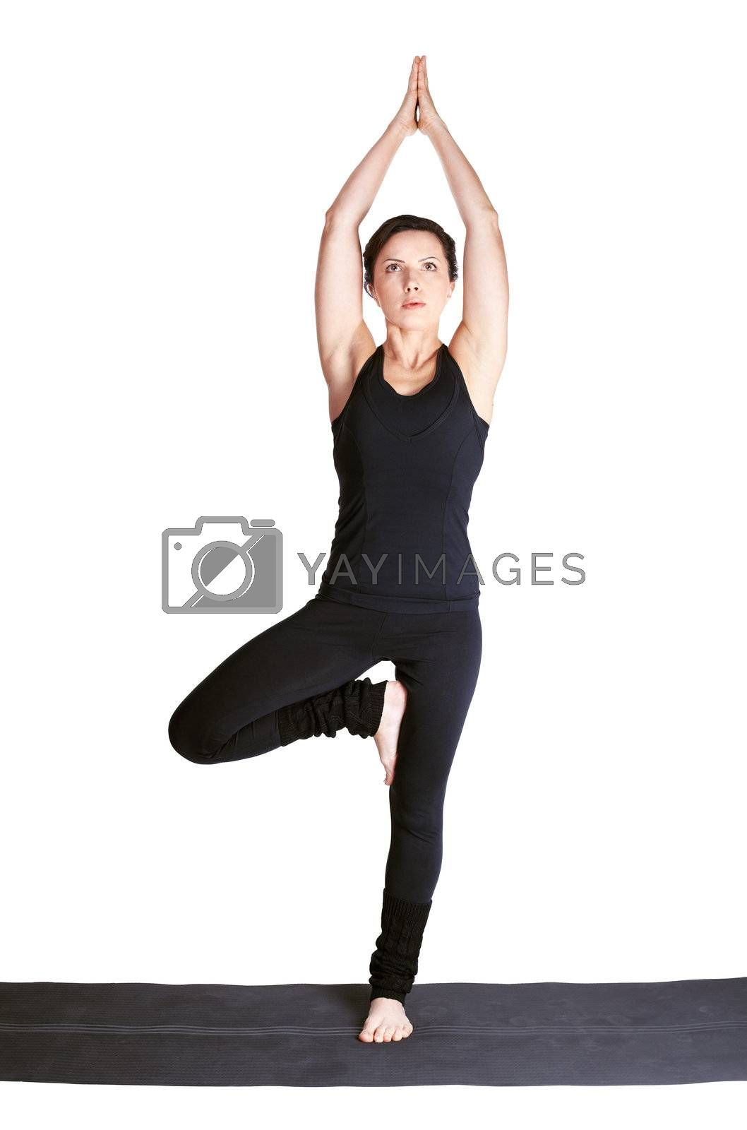 full-length portrait of beautiful woman working out yoga exercise tree-pose vrikshasana or vrksana
