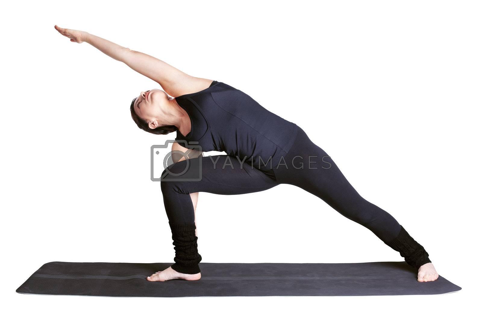 full-length portrait of beautiful woman working out yoga exercise side angle pose utthita parshvakonasana on fitness mat