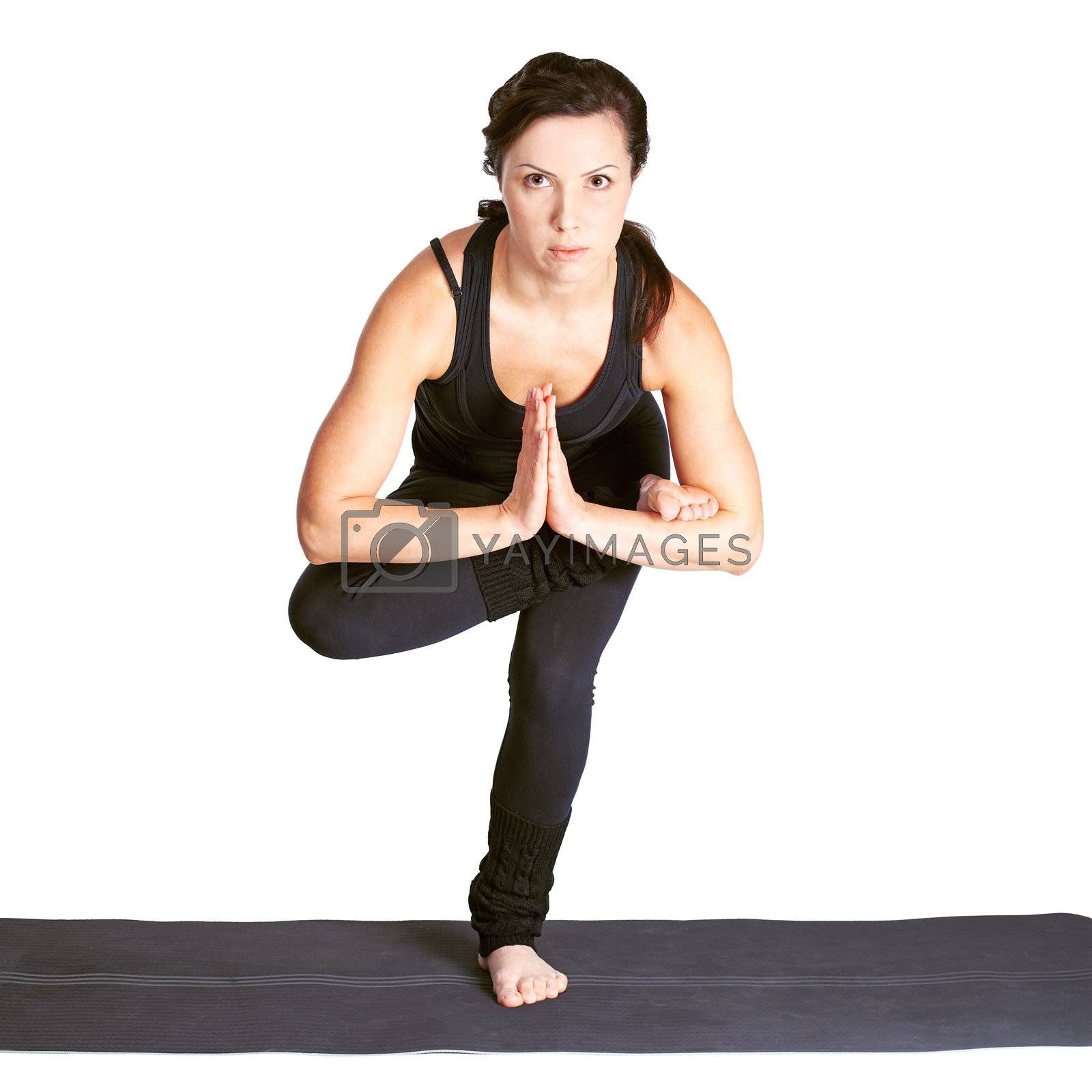 full-length portrait of beautiful woman working out yoga exercise. balancing on one leg on fitness mat