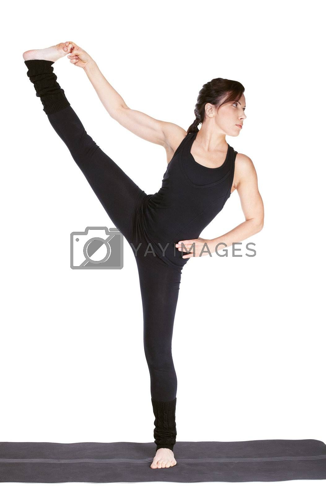 full-length portrait of beautiful woman working out yoga exercise utthita hasta padangustasana (extended hand-to-vig-toe pose). balancing on one leg on fitness mat