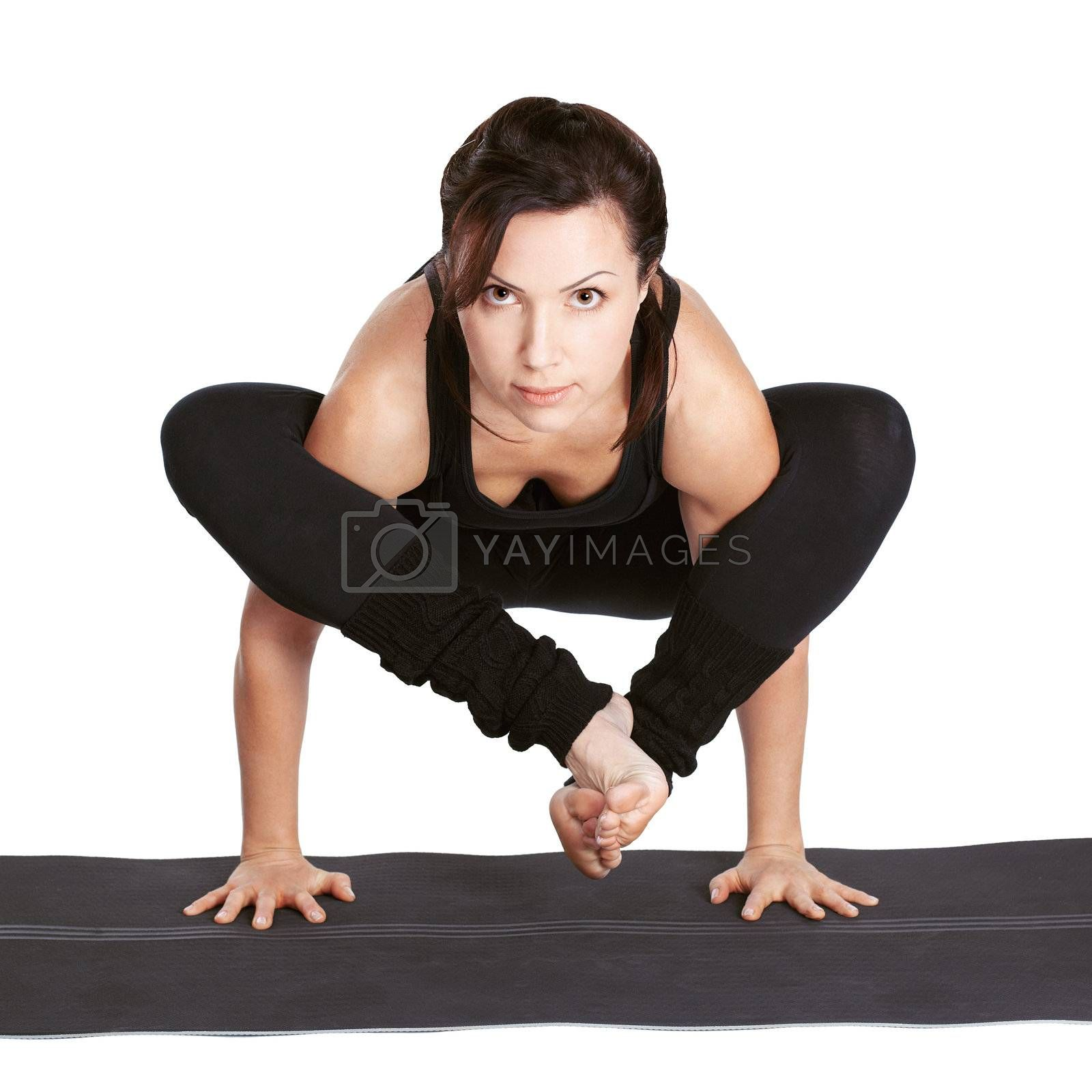 full-length portrait of beautiful woman working out yoga exercise bhujapidasana (shoulder-pressing pose) on fitness mat